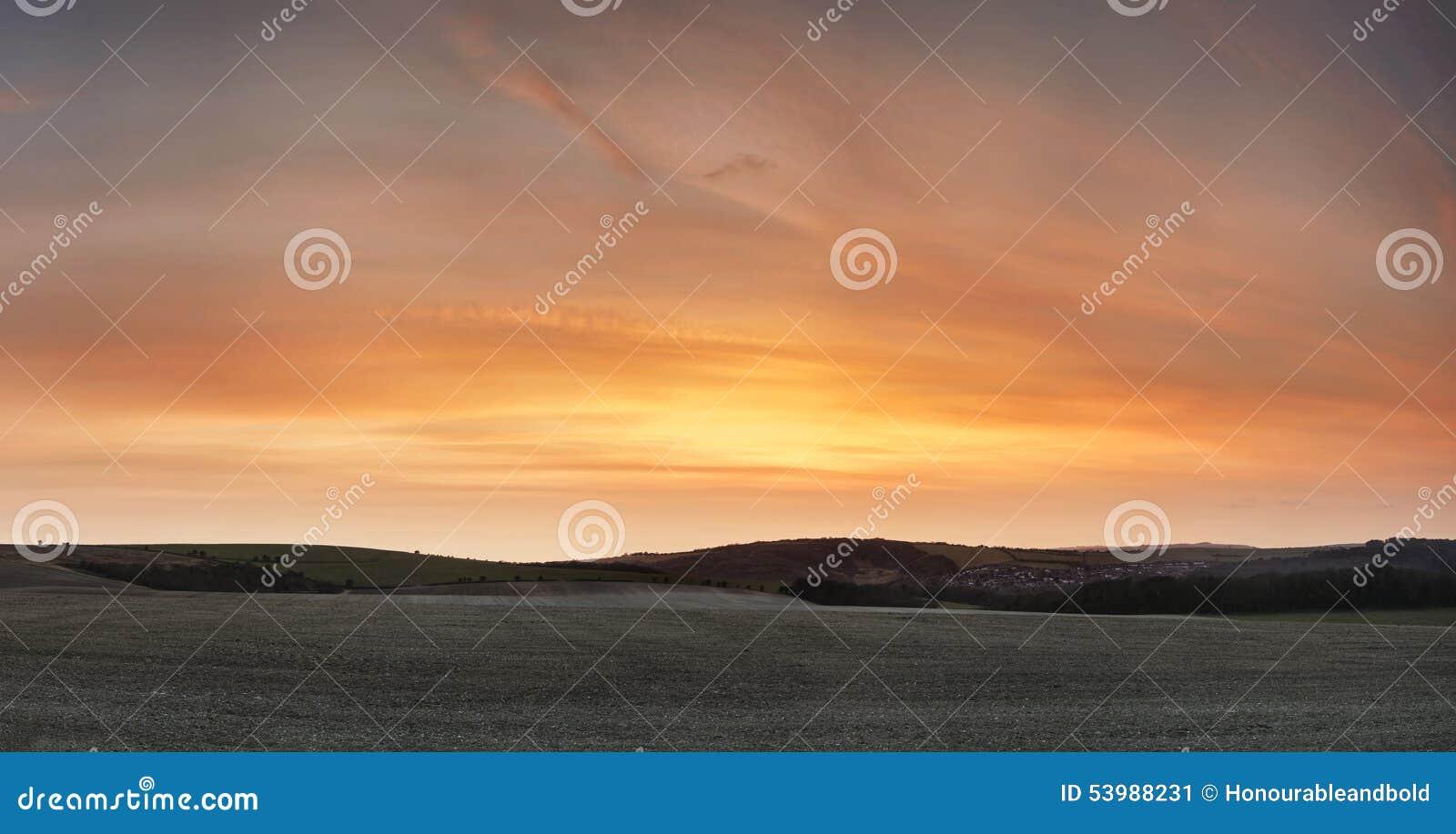 Bedöva härlig solnedgång över lantgårdlandskap med vibrerande coors