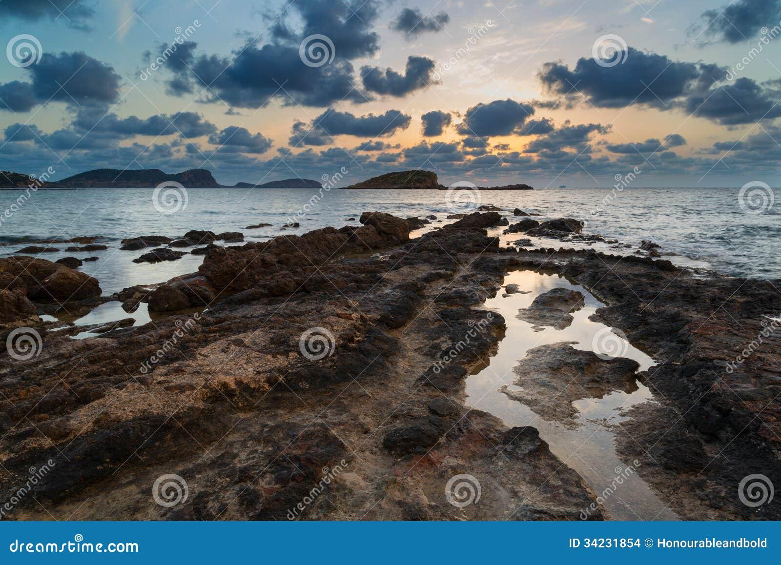Bedöva landskap gry soluppgång med den steniga kustlinjen och lång exp