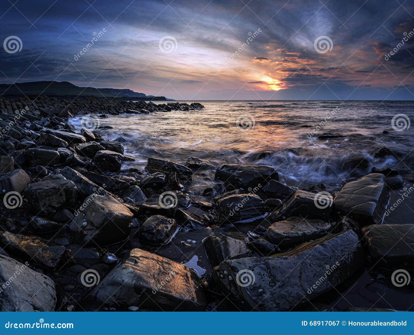 Bedöva solnedgånglandskapbild av den steniga kustlinjen