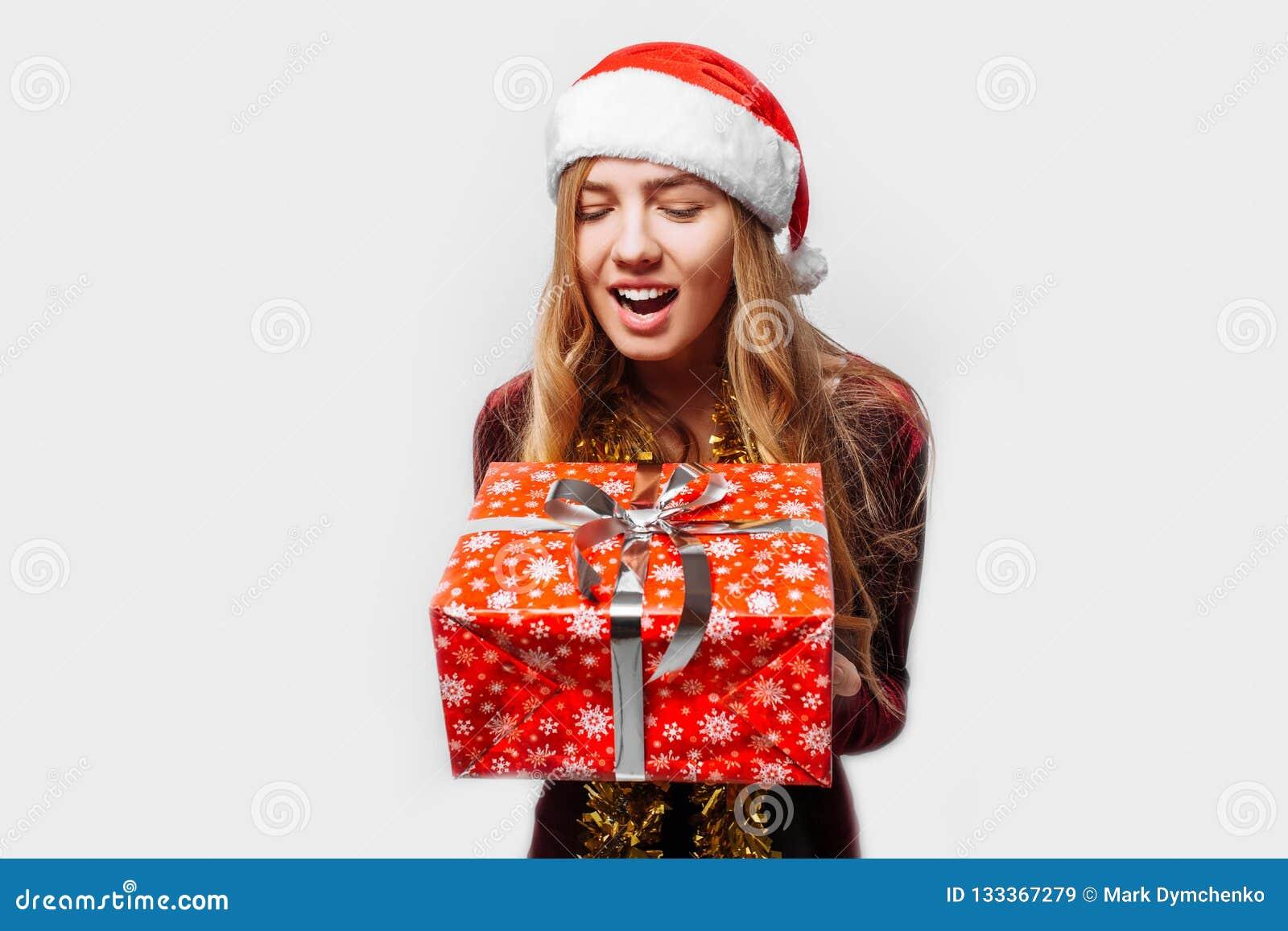 Bedövad flicka i en hatt av Santa Claus, i hennes händer - jul