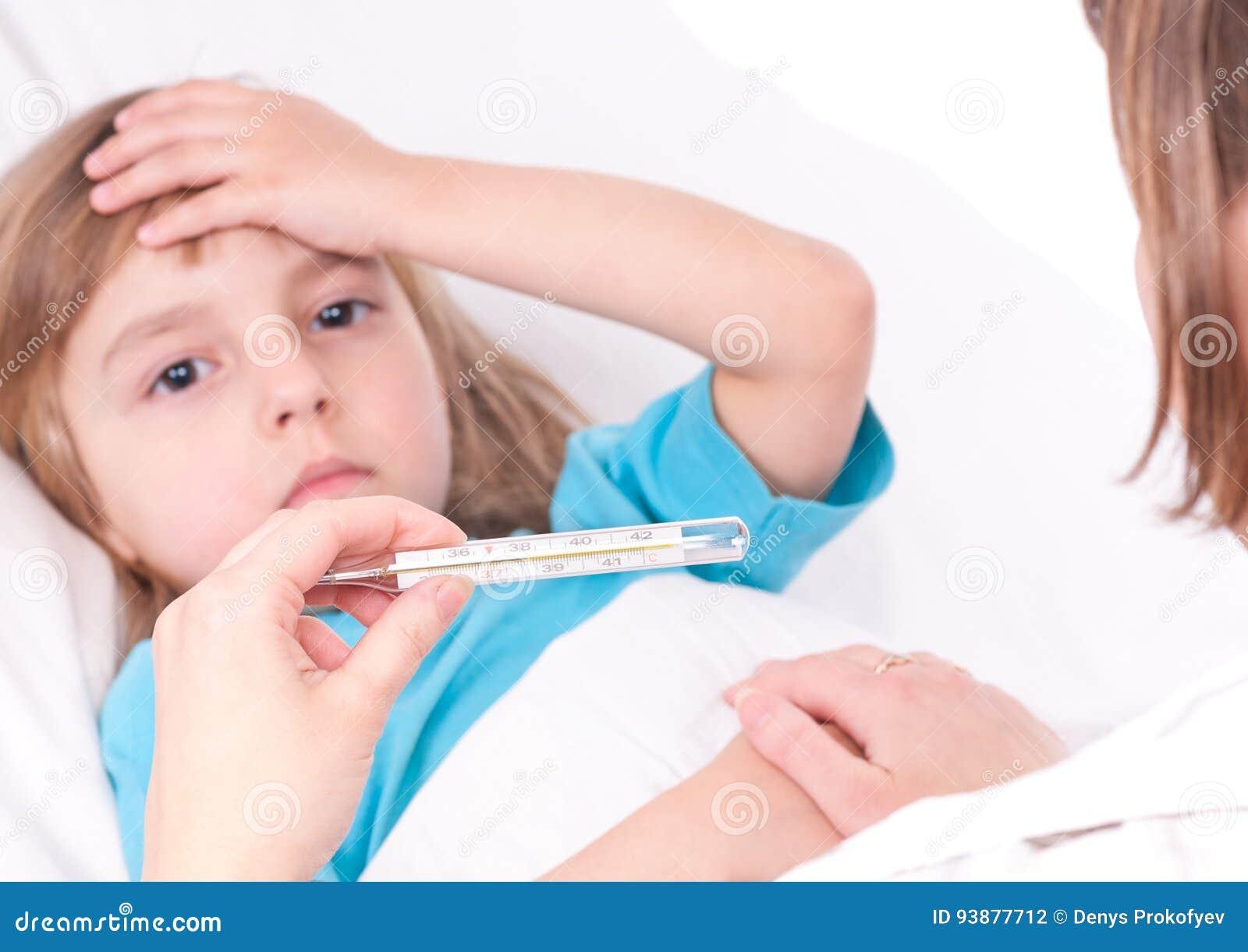 Bed den små modern för flickan nära den sjuka sittande termometern