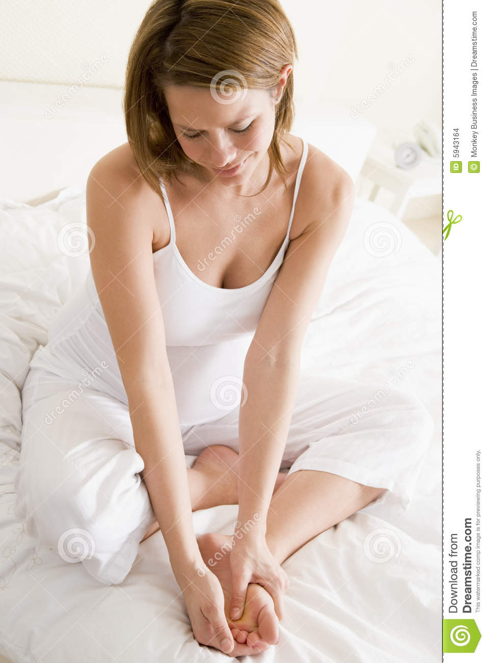 Bed feet pregnant rubbing smiling woman
