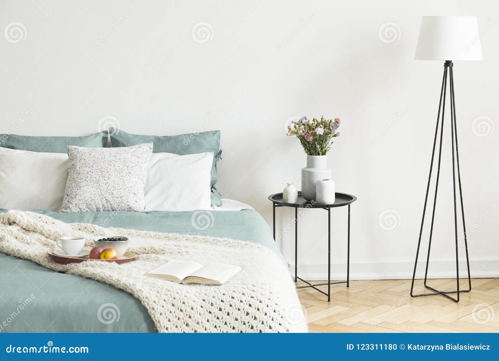 Bed met theekop, appelen en bosbessen op ontbijtdienblad en o