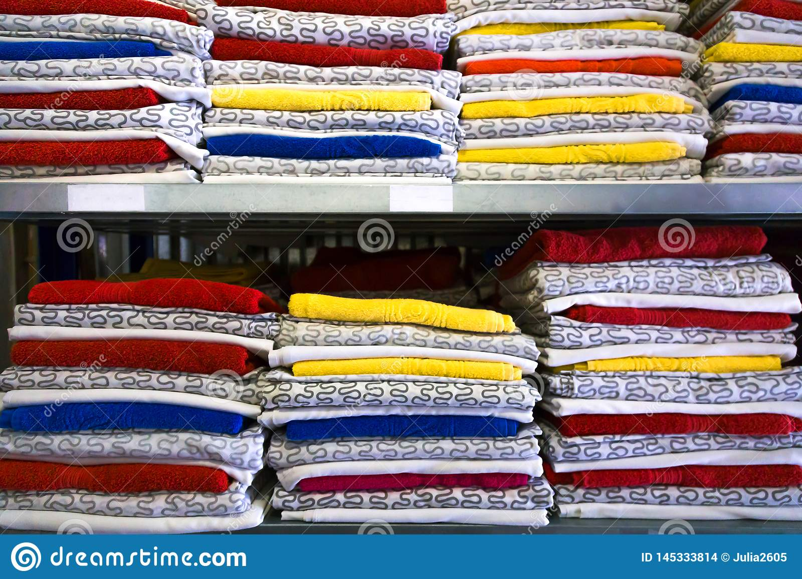 Bedding is in the closet on the shelf. Towels folded in a roll. On hangers hanging ladies` and men`s clothing.