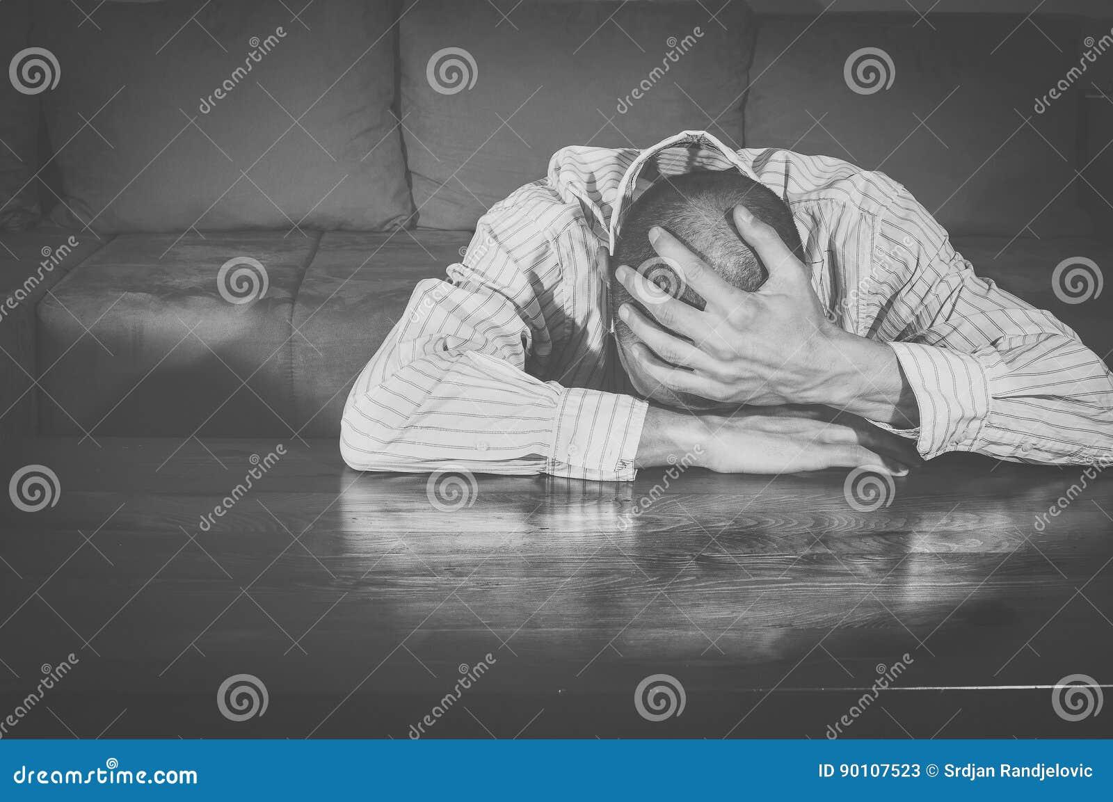 Bedrövligt sammanträde för ung man i hans rum Fördjupning svart white ensamhet sorgsenhet förvirring skriande man Ledset manskrik