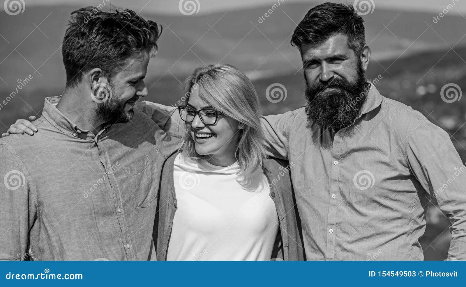 Bedrijf van drie gelukkige collega s of partnersomhelzingen openlucht, aardachtergrond Mensen met baard in formele overhemden en