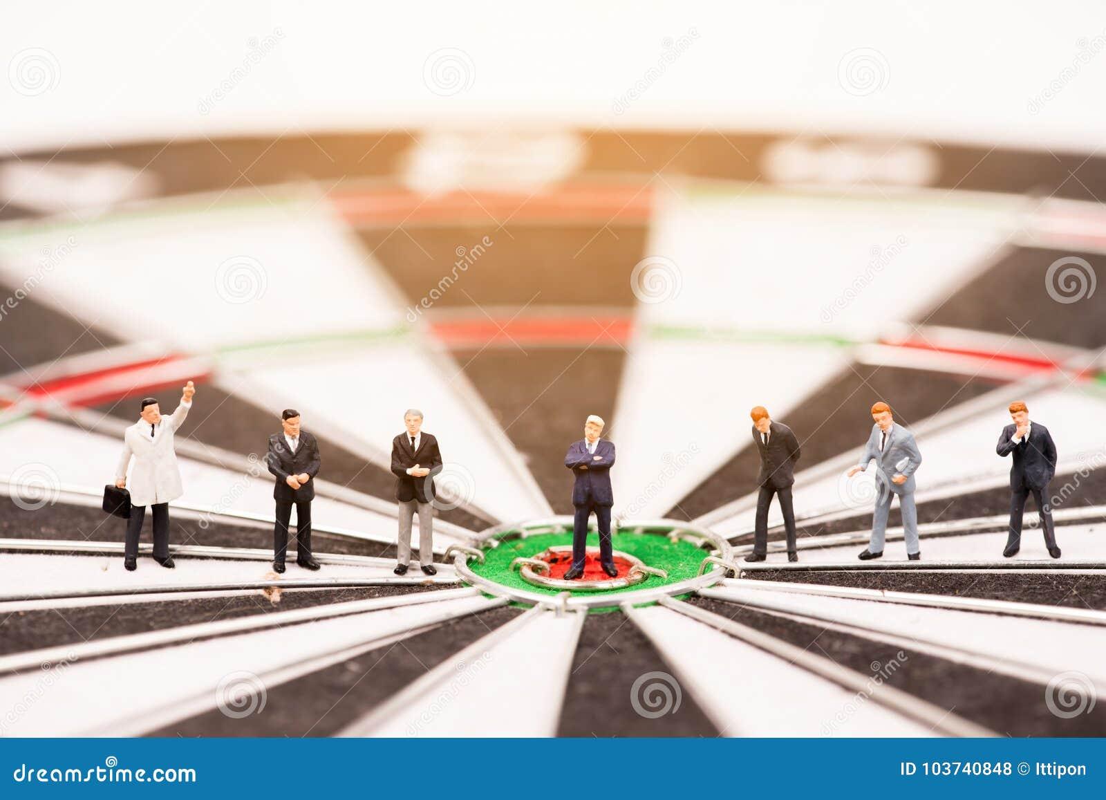 Bedrijfs miniatuurmensen die zich op dartboard bevinden