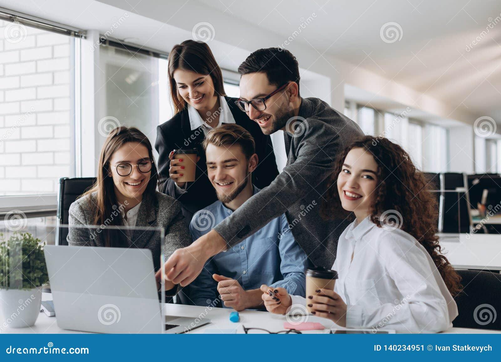 Bedrijfsberoeps Groep jonge zekere bedrijfsmensen die gegevens analyseren die computer met behulp van terwijl het doorbrengen van
