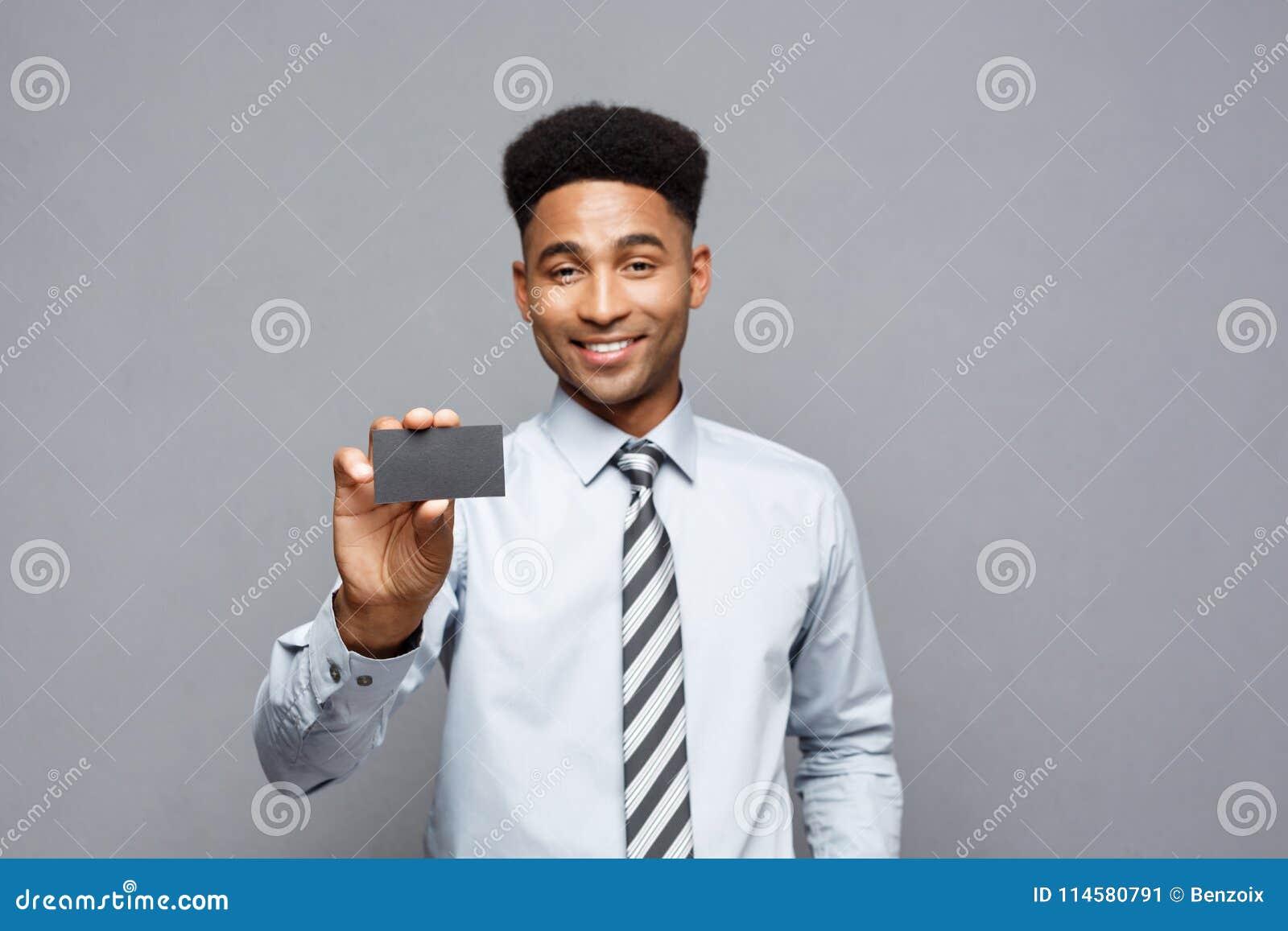 Bedrijfsconcept - Gelukkige knappe professionele Afrikaanse Amerikaanse zakenman die naamkaart tonen aan cliënt