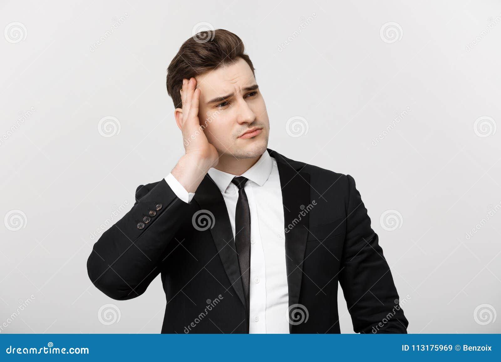 Bedrijfsconcept: Jonge die zakenman met holdingshanden op hoofd met hoofdpijngelaatsuitdrukking over wit wordt geïsoleerd