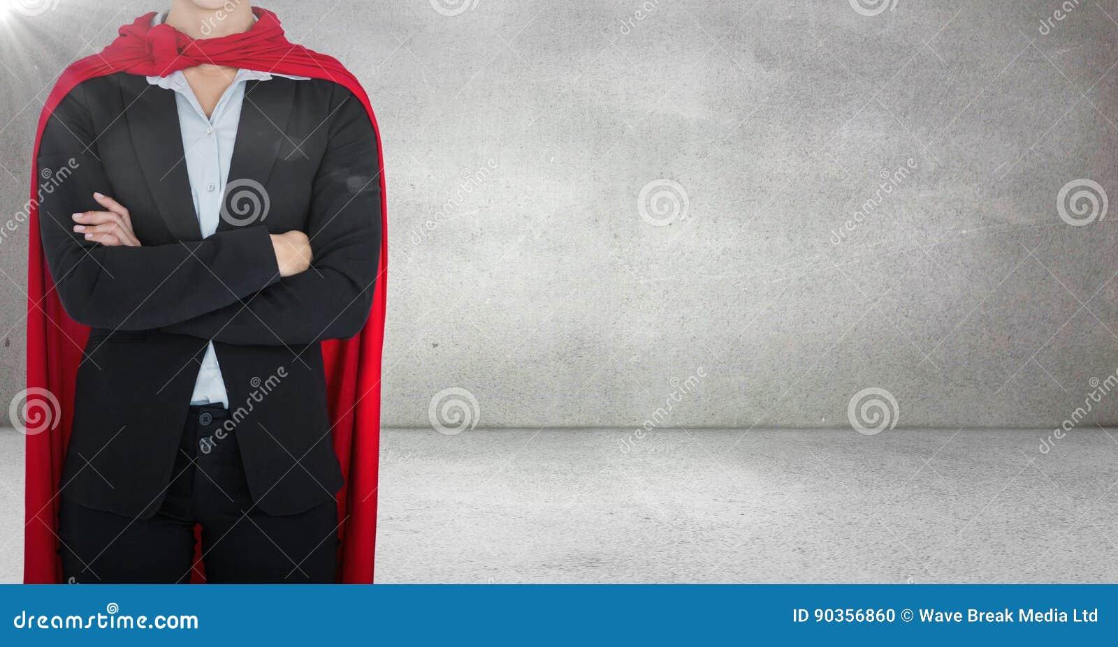 Bedrijfsdievrouwensuperhero met wapens tegen grijze muur met gloed worden gevouwen