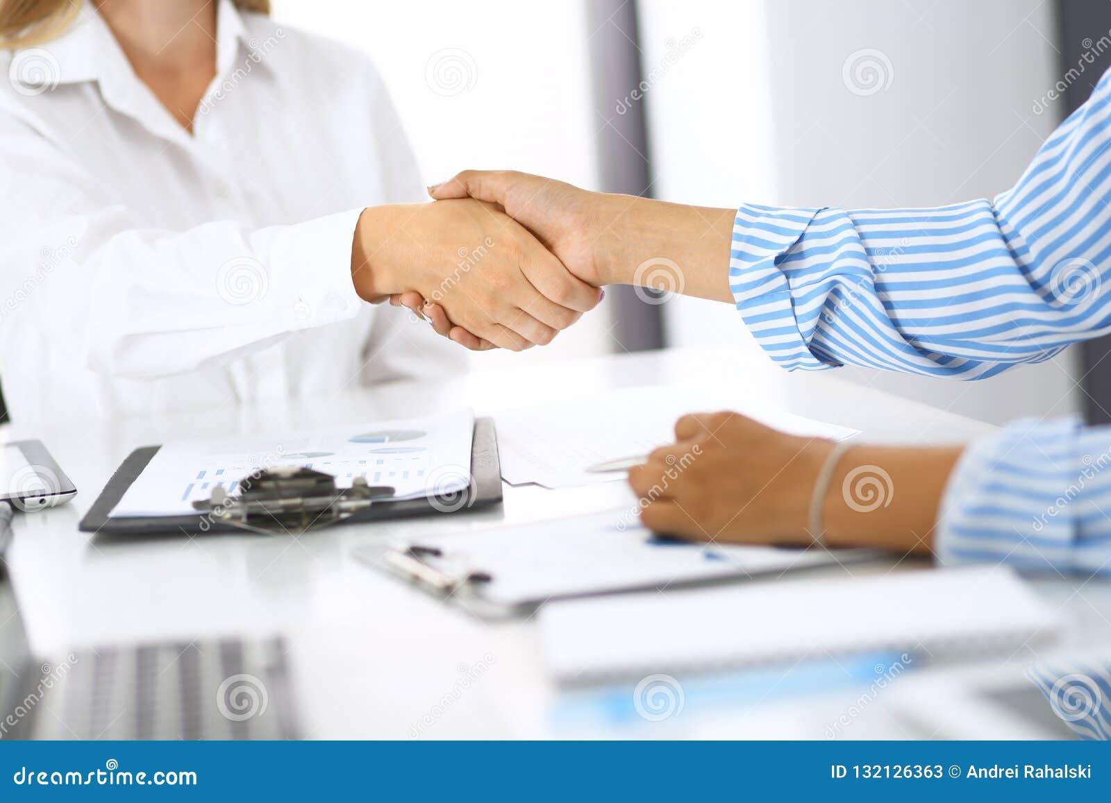 Bedrijfshanddruk bij vergadering of onderhandeling in bureau Assoieert het schudden handen terwijl tevreden omdat ondertekenend c