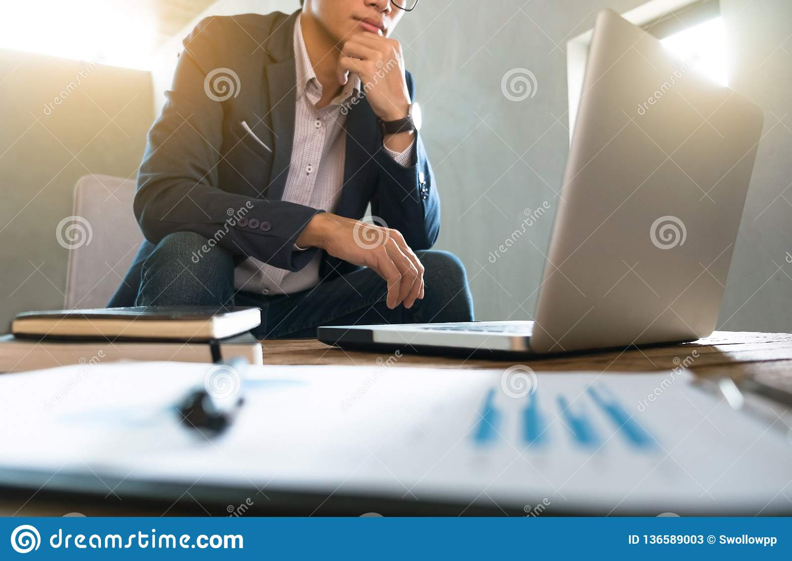 Bedrijfsmens die aan bedrijfsdocument en laptop op het werk werken