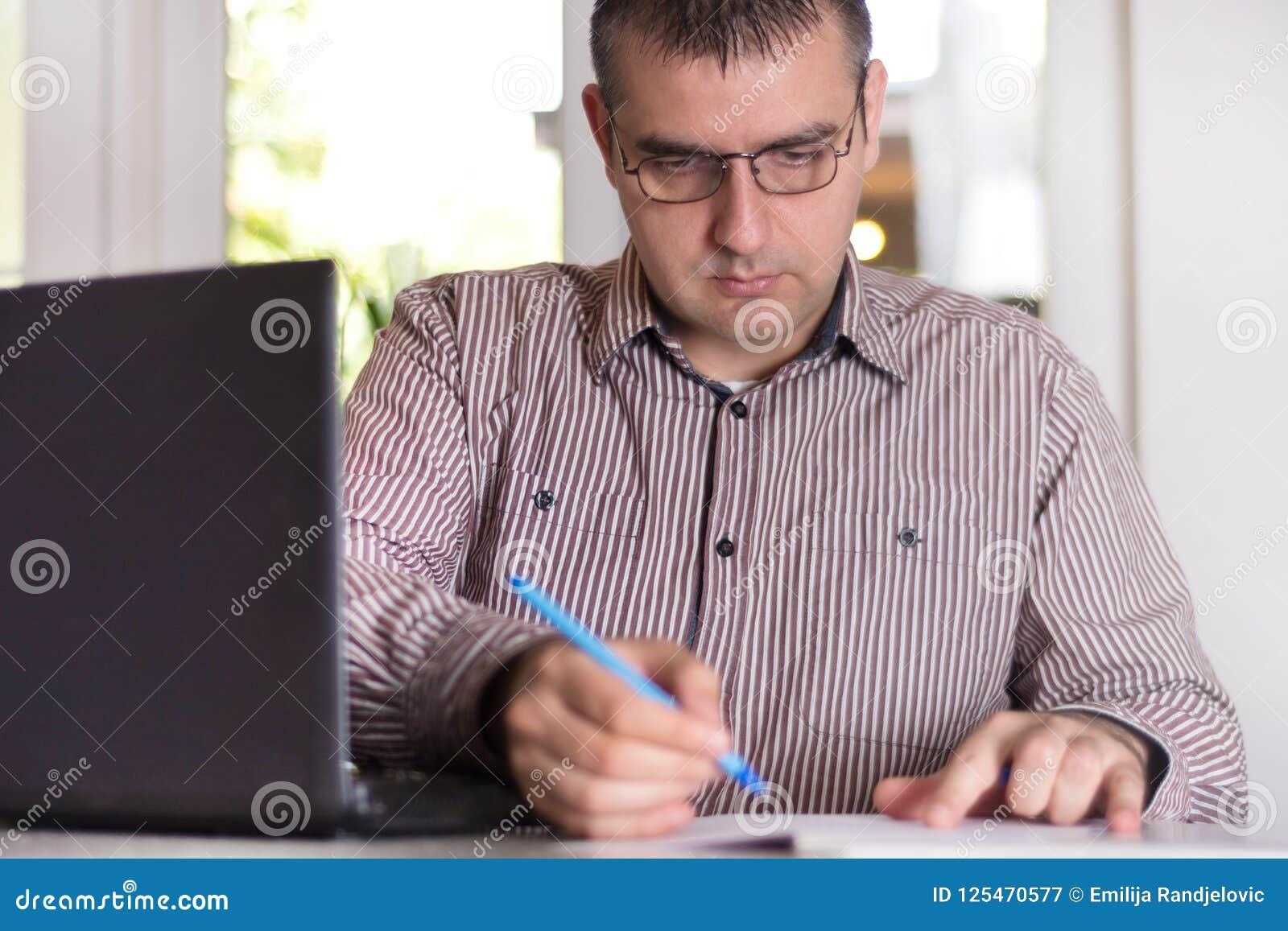 Bedrijfsmens die op modern kantoor met documenten en laptop werken