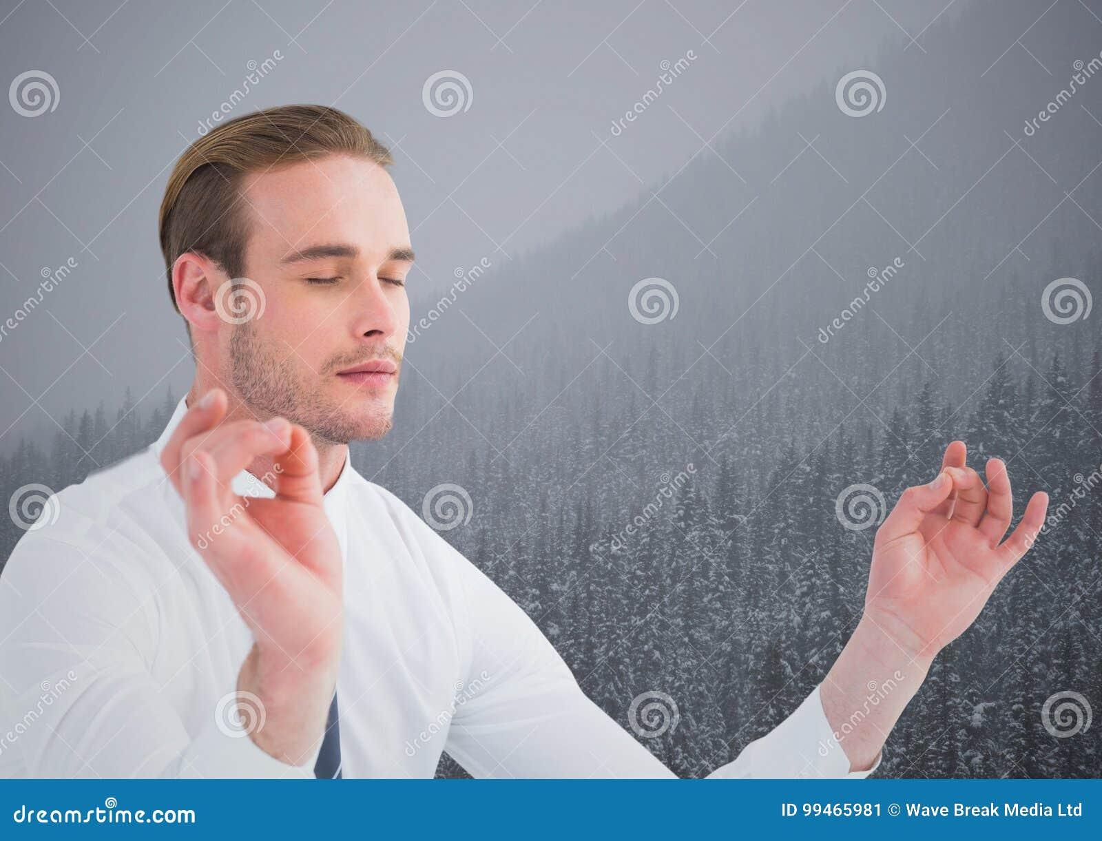 Bedrijfsmens die tegen heuvels met bomen en grijze hemel mediteren