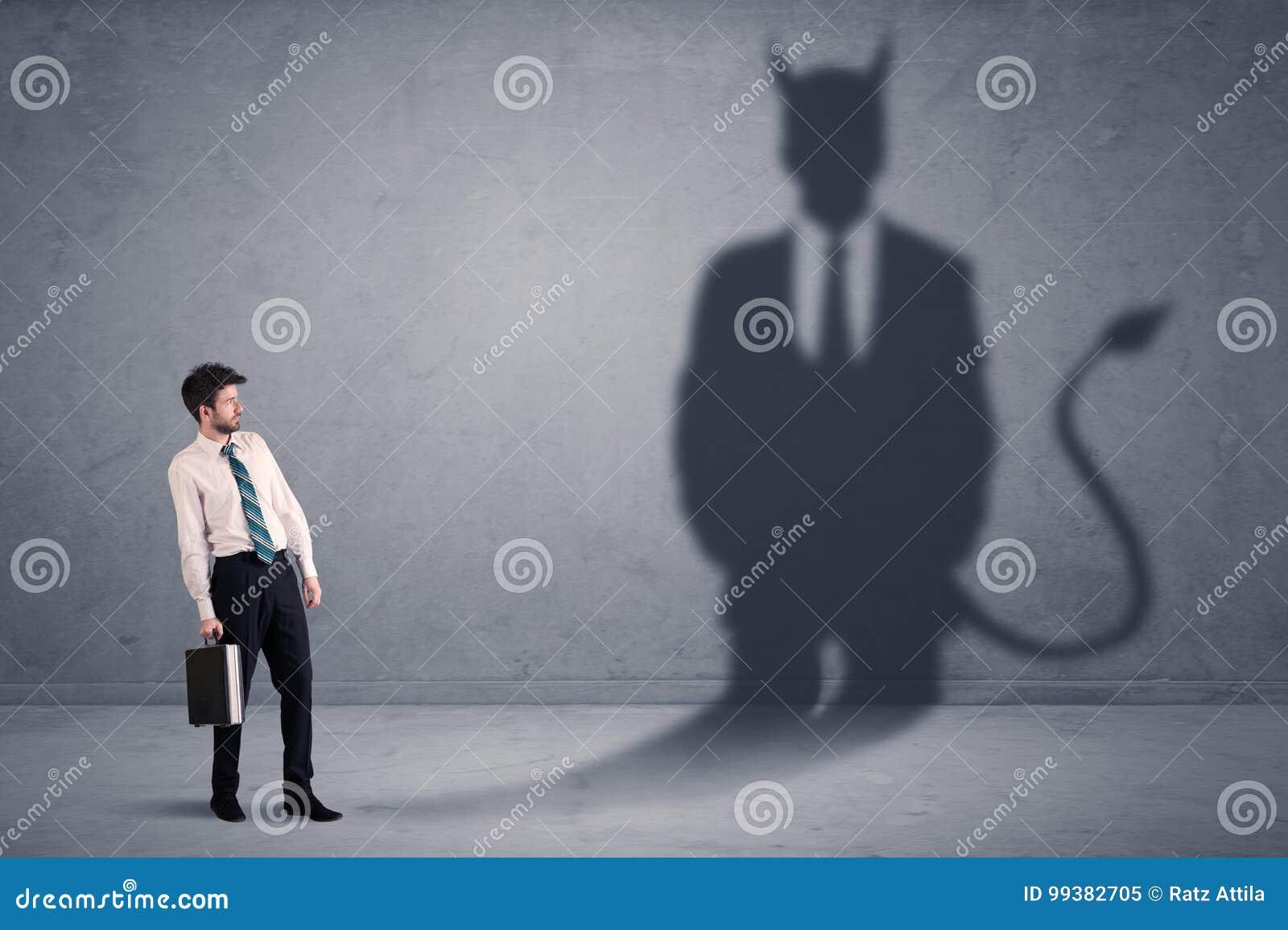 Bedrijfsmens die zijn eigen de schaduwconcept van het duivelsdemon bekijken