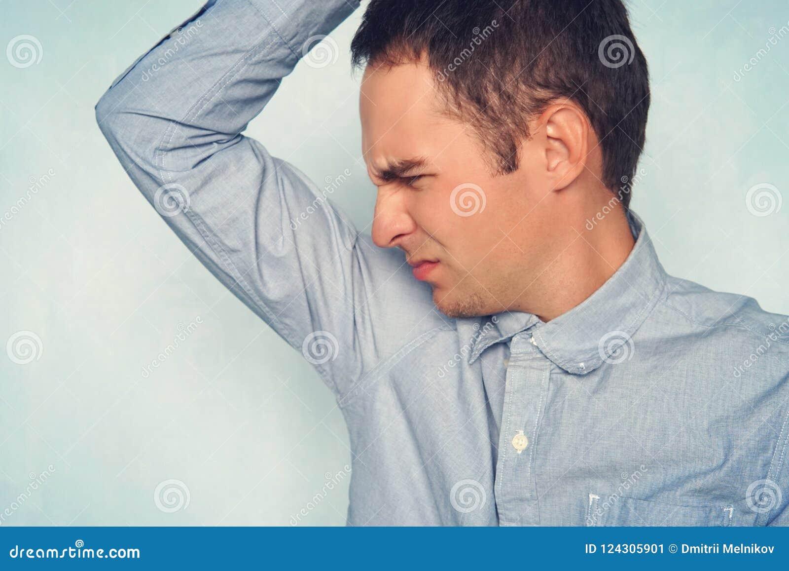 Bedrijfsmens met het zweten onder oksel in blauw overhemd de jonge kerel snuift zijn oksels en maakt een ontstemde uitdrukking