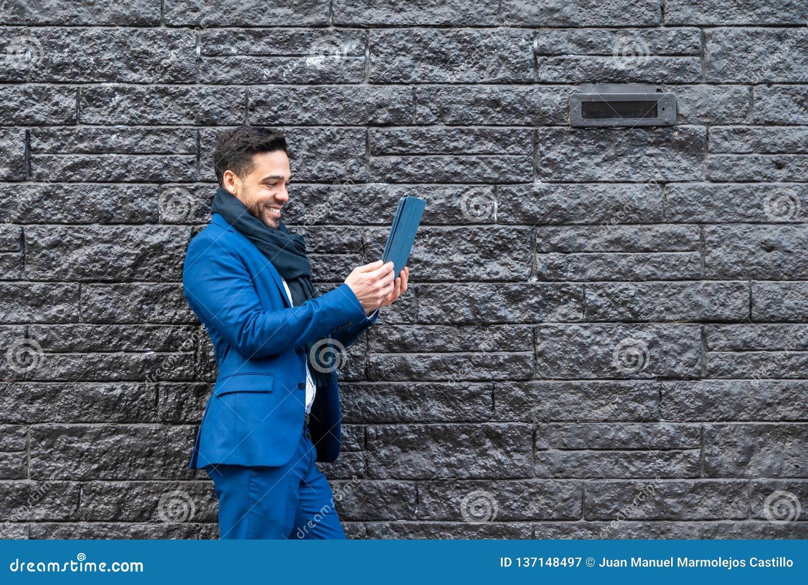 Bedrijfsmens op blauw kostuum die beeld met tablet nemen