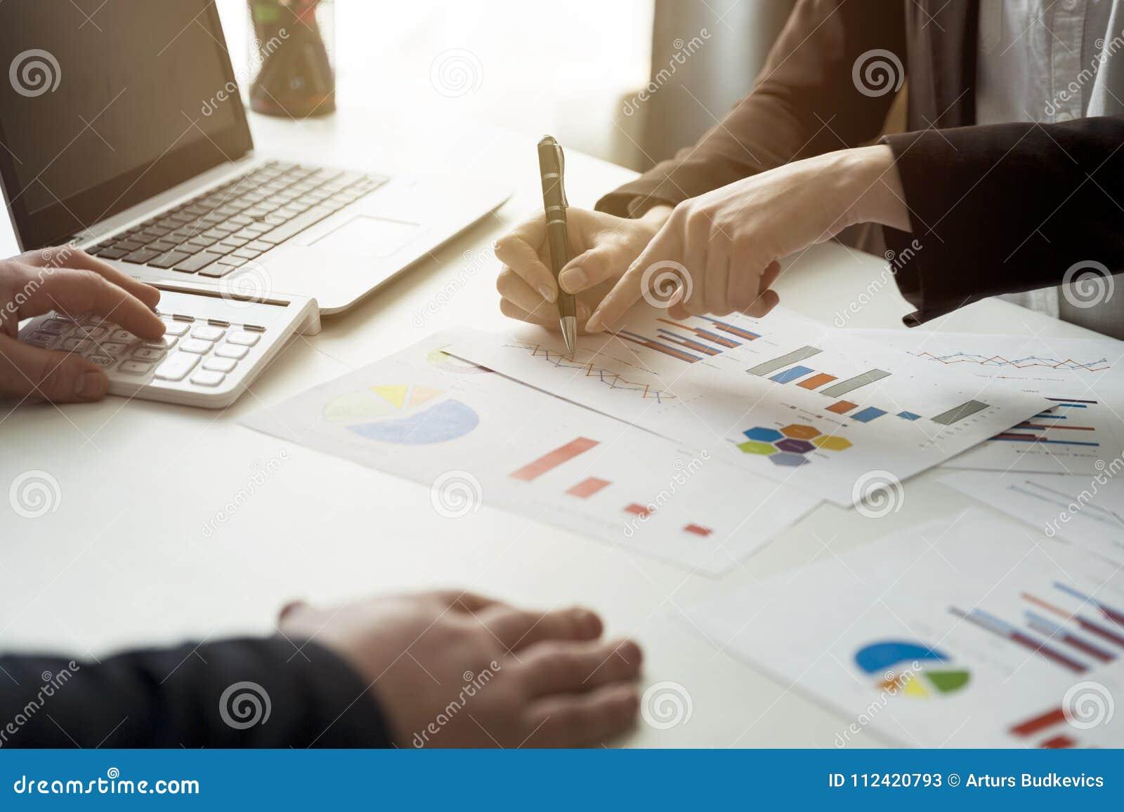 Bedrijfsmensen die de grafieken en de grafieken bespreken die onderzoek tonen