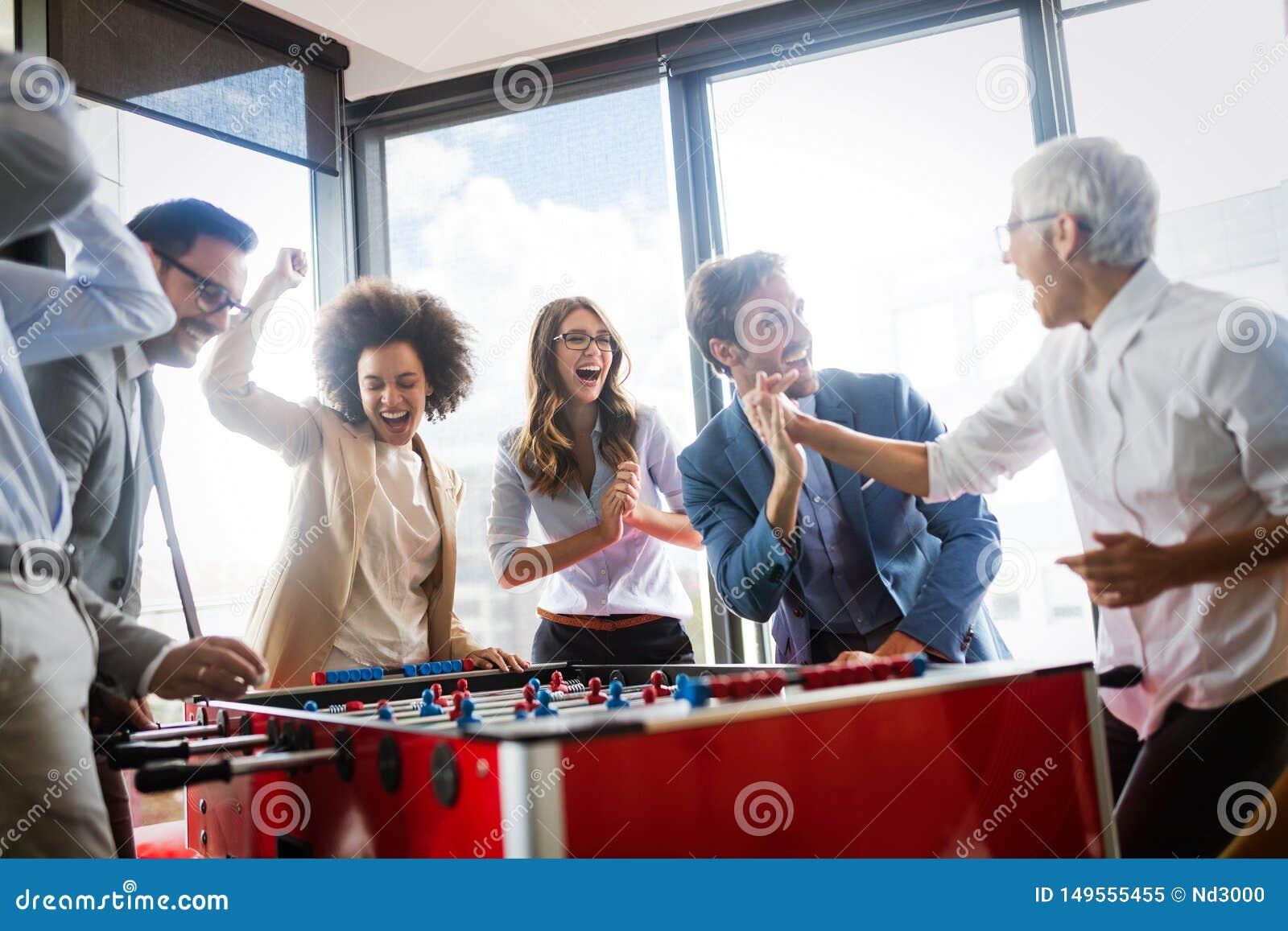 Bedrijfsmensen die grote tijd hebben samen Collega s die lijstvoetbal in modern bureau spelen