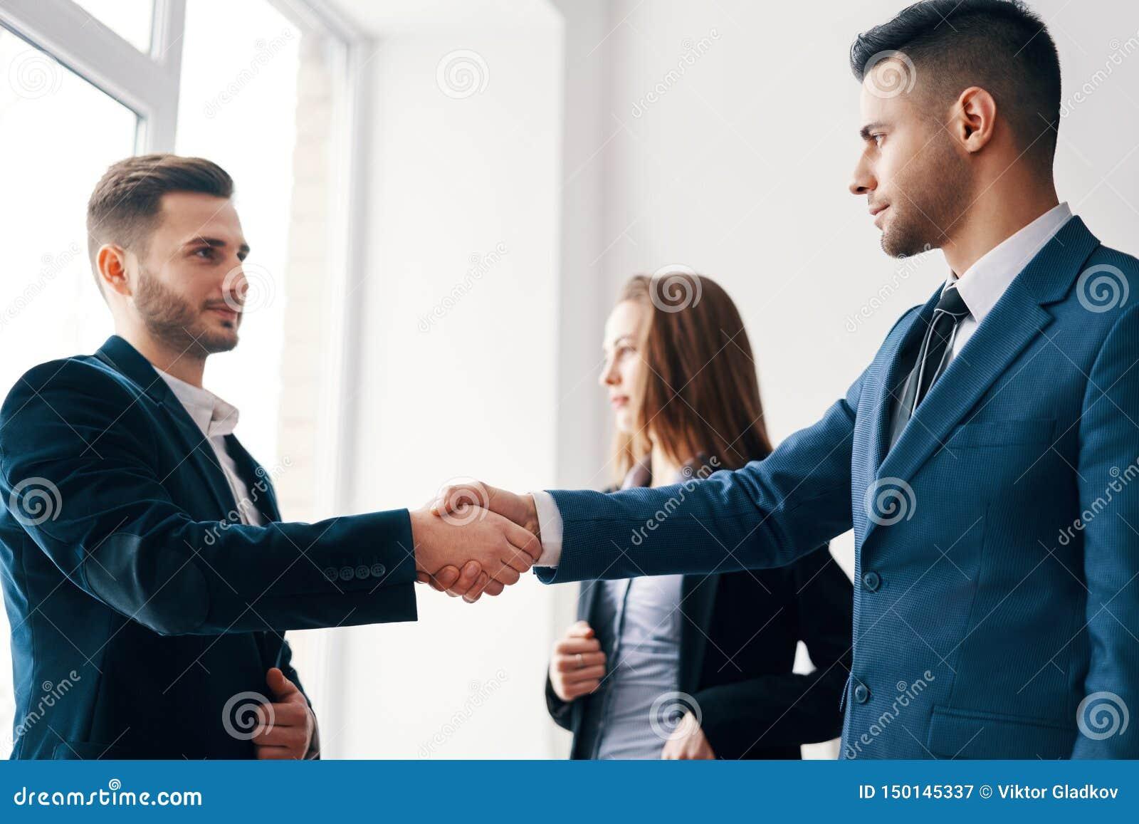Bedrijfsmensen die handen na goede overeenkomst schudden