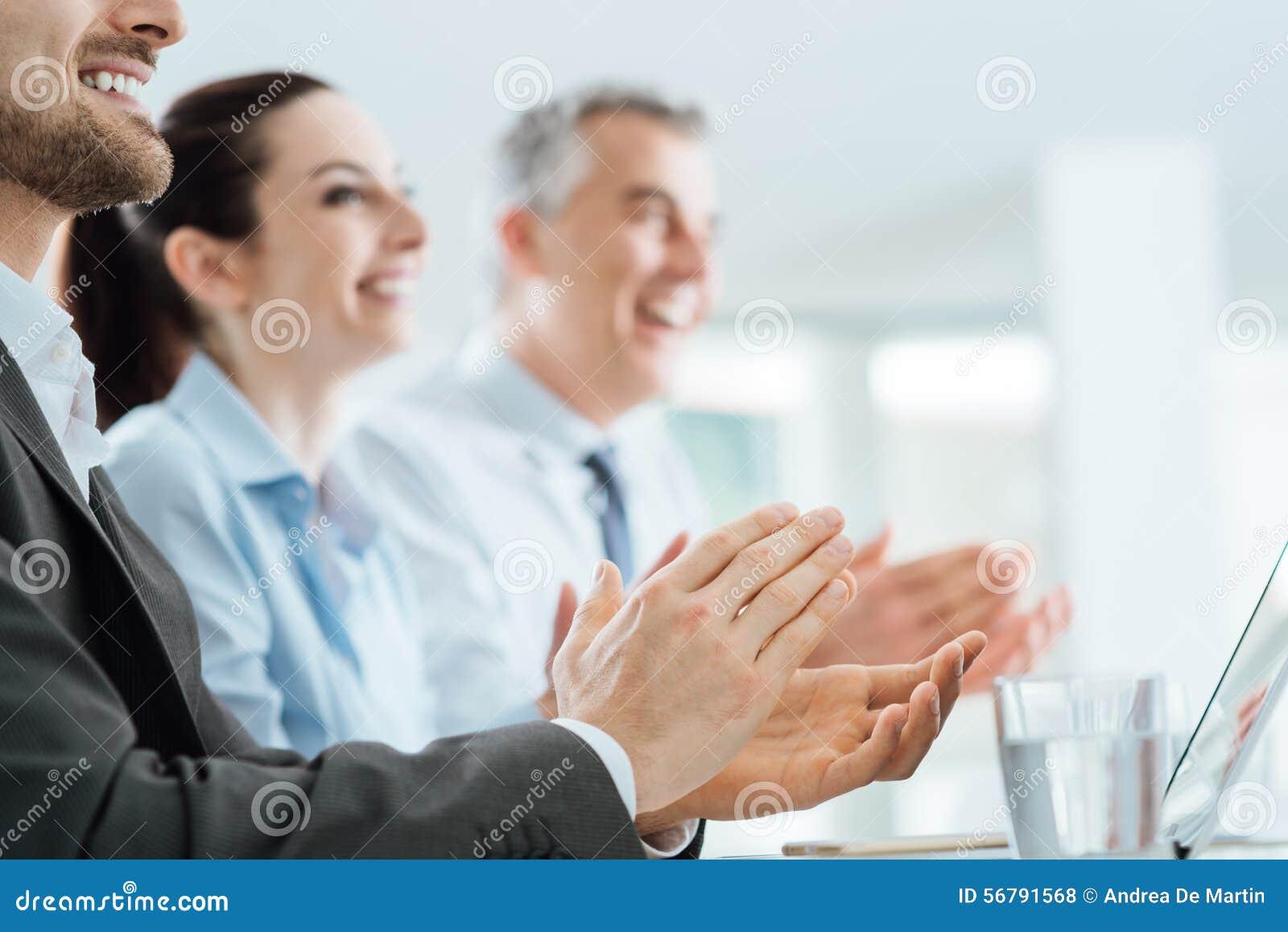 Bedrijfsmensen die handen slaan tijdens een seminarie
