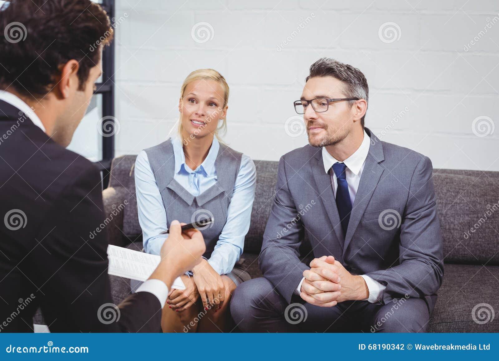 Bedrijfsmensen die terwijl het zitten op bank bespreken