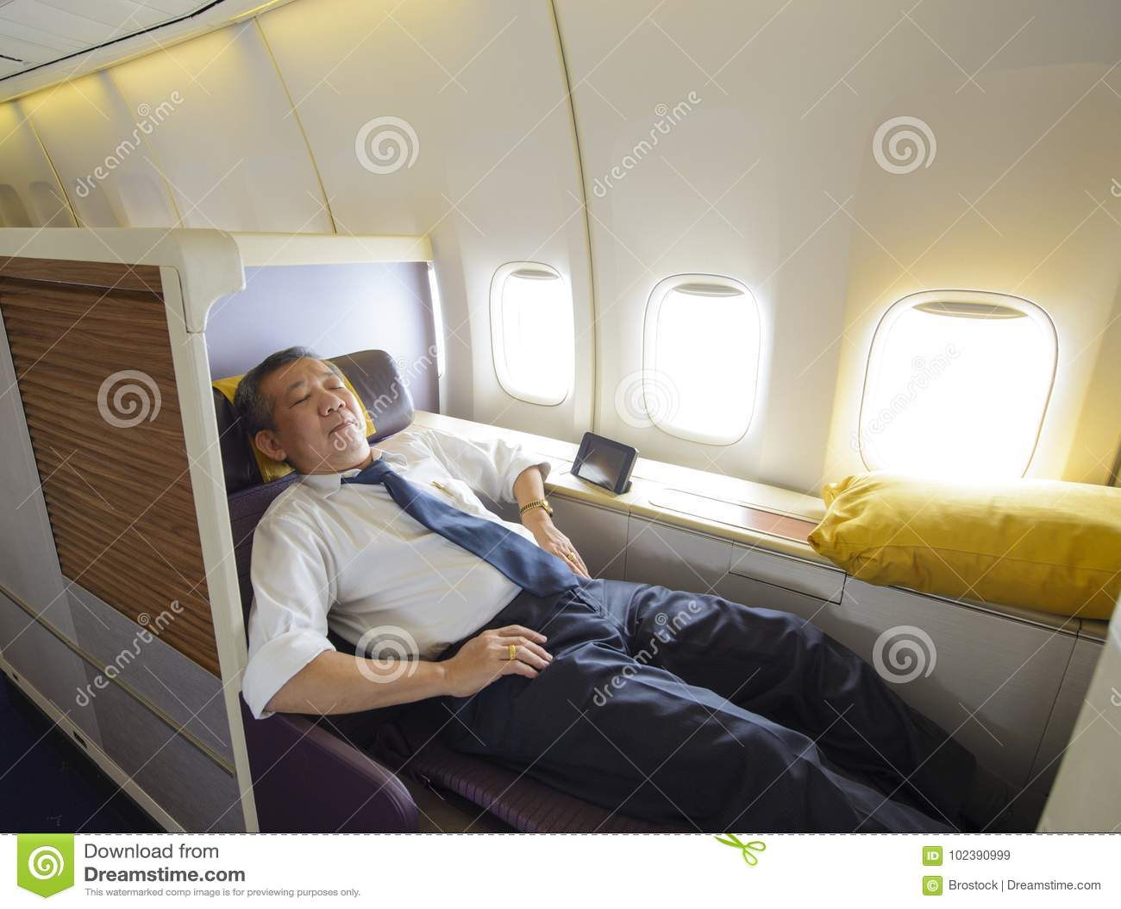 Bedrijfsmensenslaap bij de eerste klasse van vliegtuig in comfortabele enige zetel