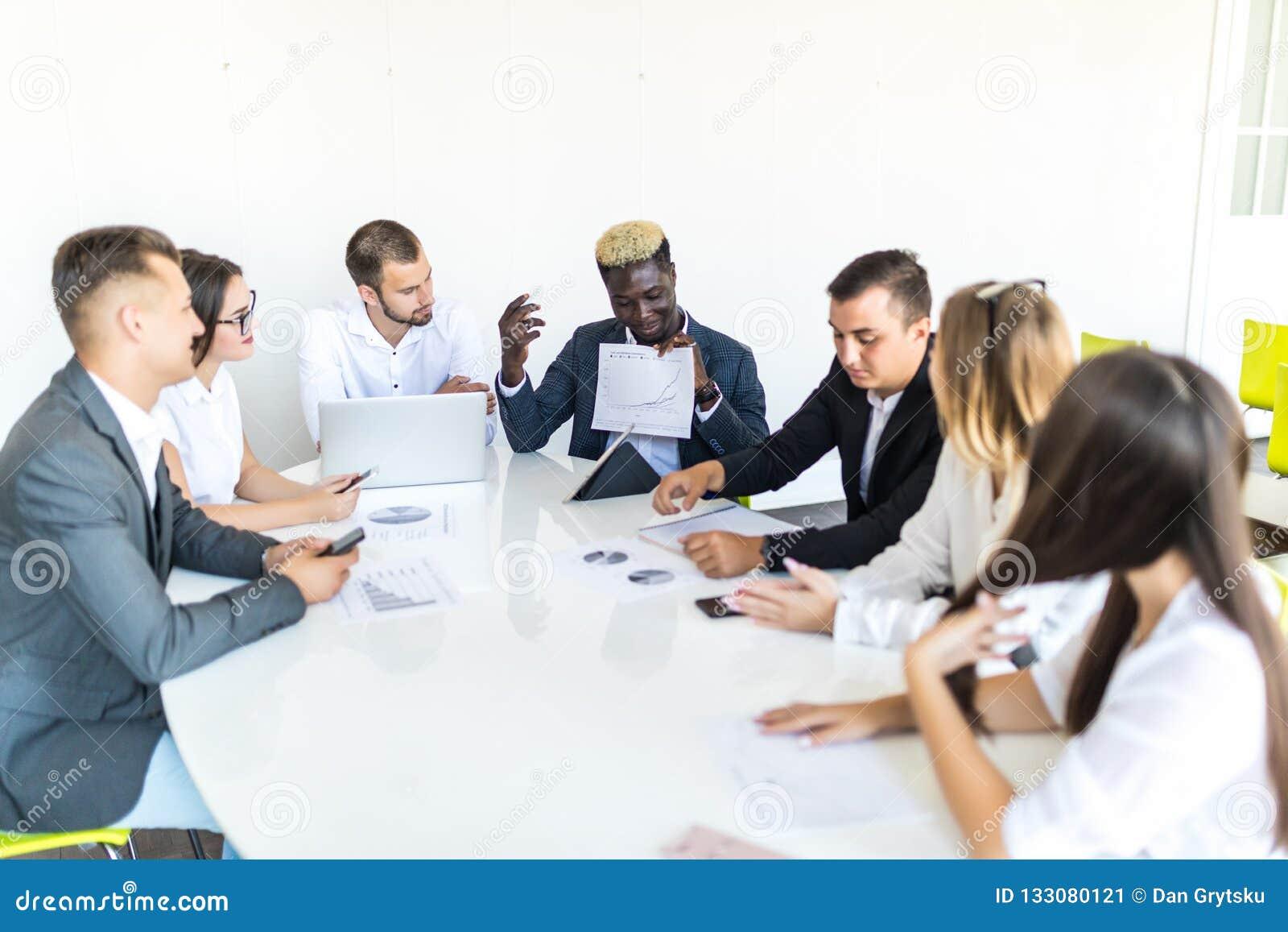 Bedrijfsmensenteam bij vergaderings werkdocumenten samen in bureau Het definitieve project komt samen