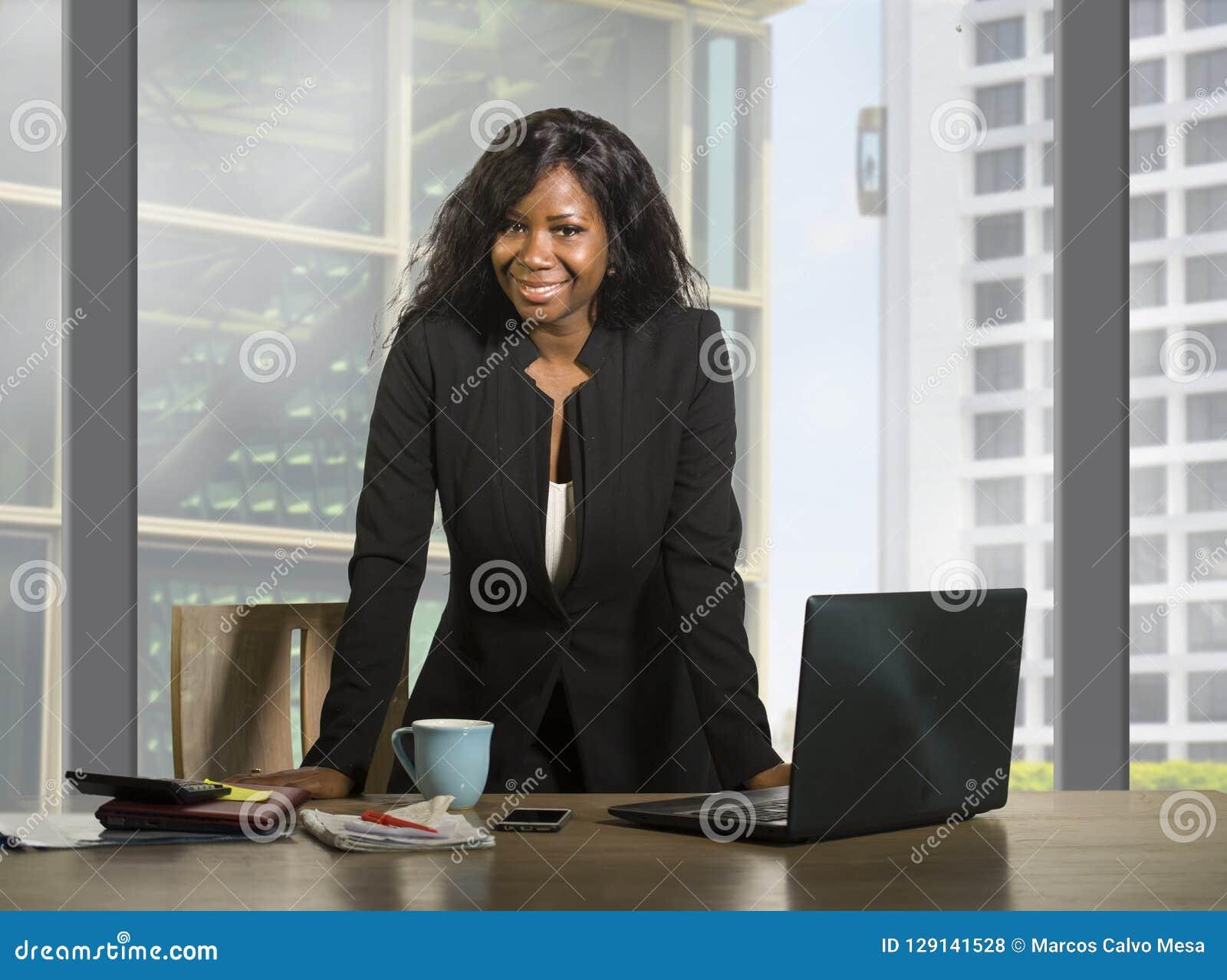 Bedrijfsportret van jonge gelukkige aantrekkelijke zwarte Afrikaanse Amerikaanse onderneemster die zekere status glimlachen succe
