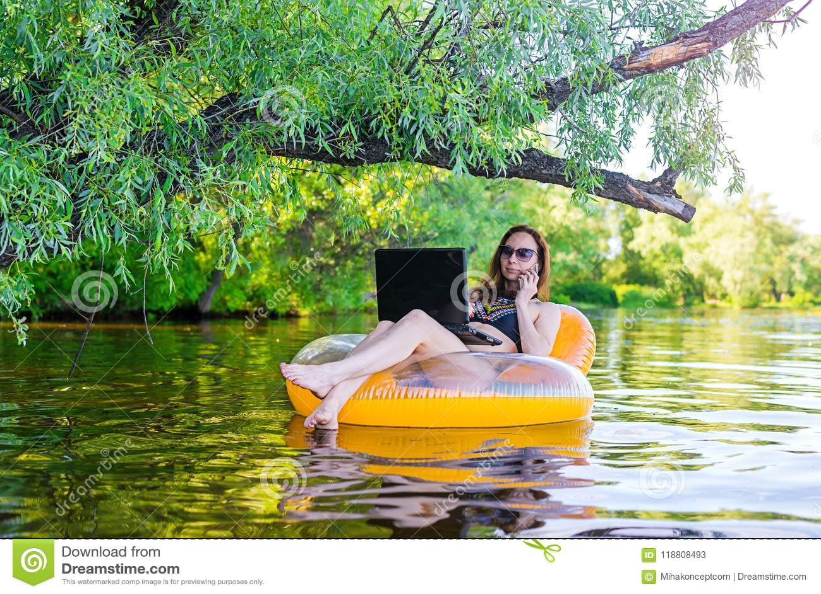 Bedrijfsvrouw die aan laptop werken en op smartphone in een opblaasbare ring in het water, een exemplaar spreken van de vrije rui