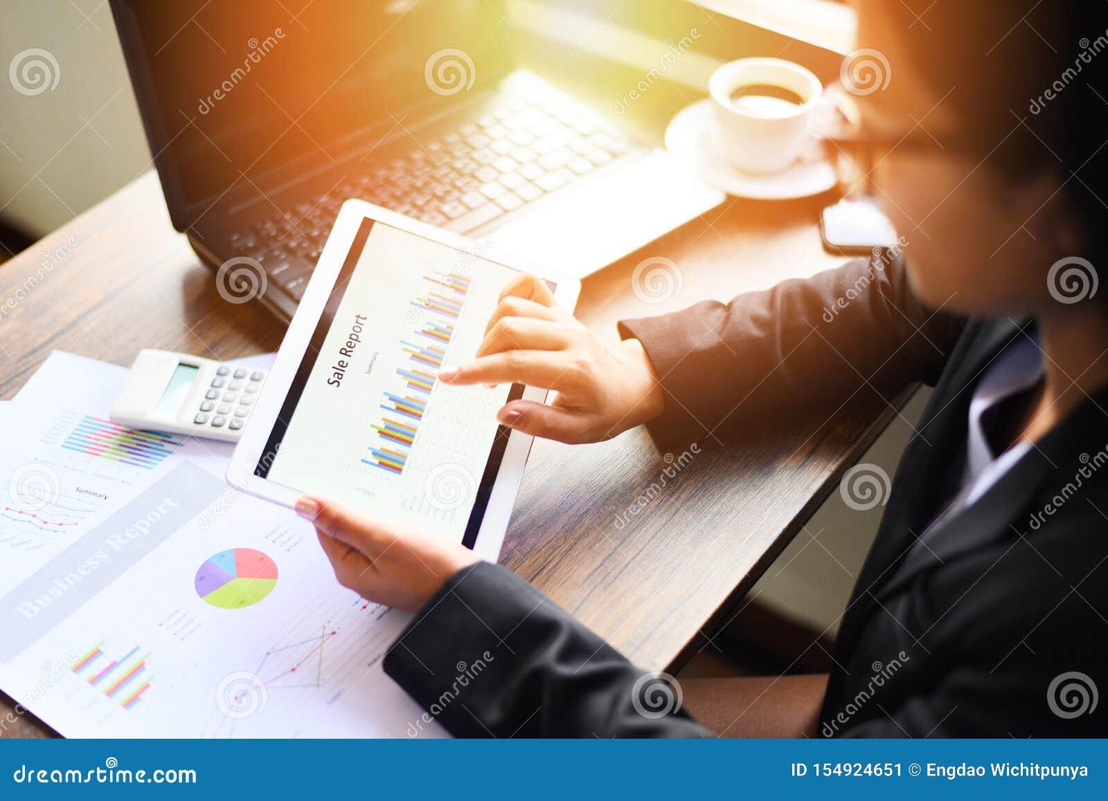 Bedrijfsvrouw die in bureau met het controleren van bedrijfsrapport werken die laptop van de tabletcomputertechnologie met calcul
