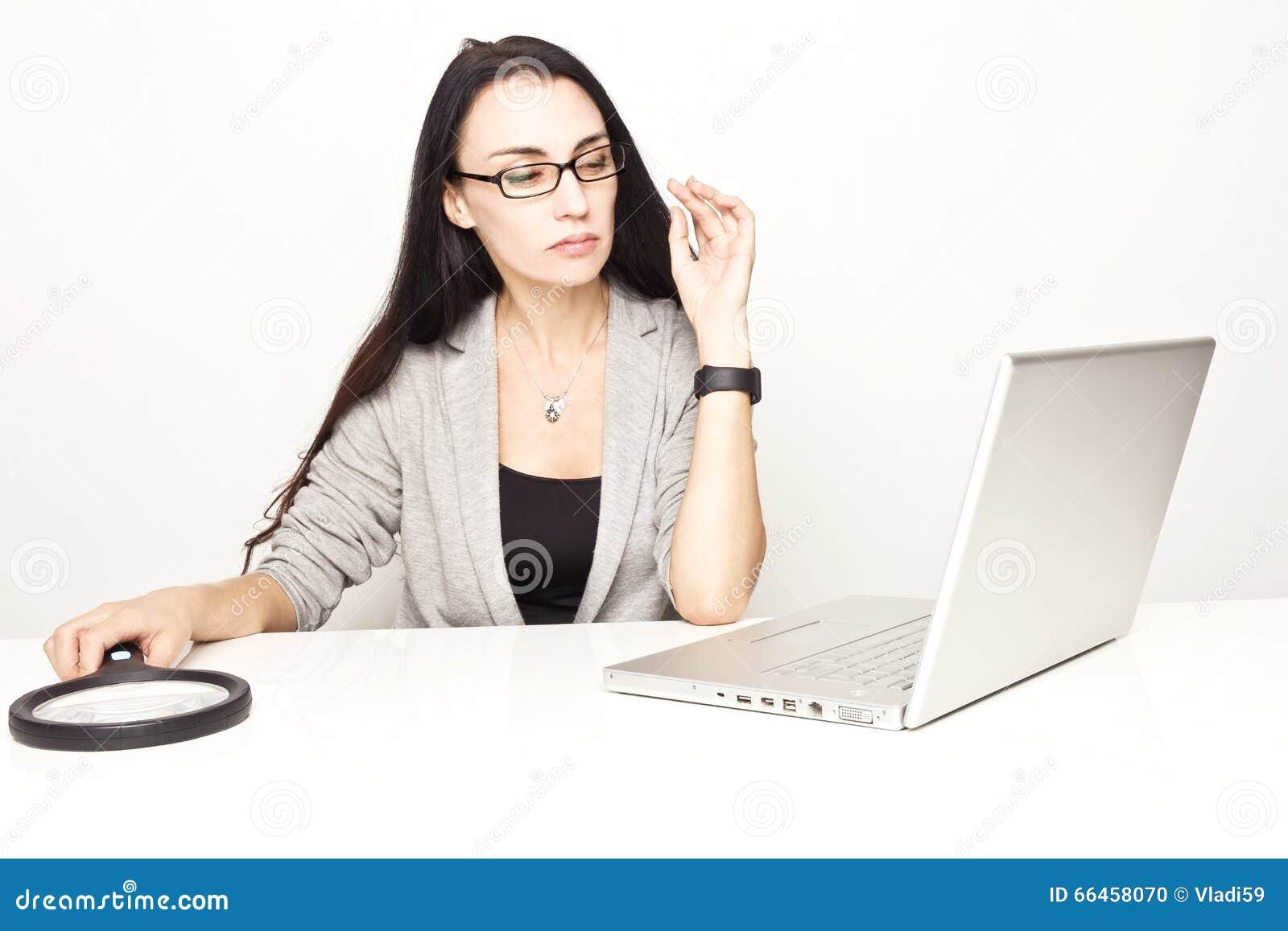 Bedrijfsvrouw die computer controleren die loupe gebruiken