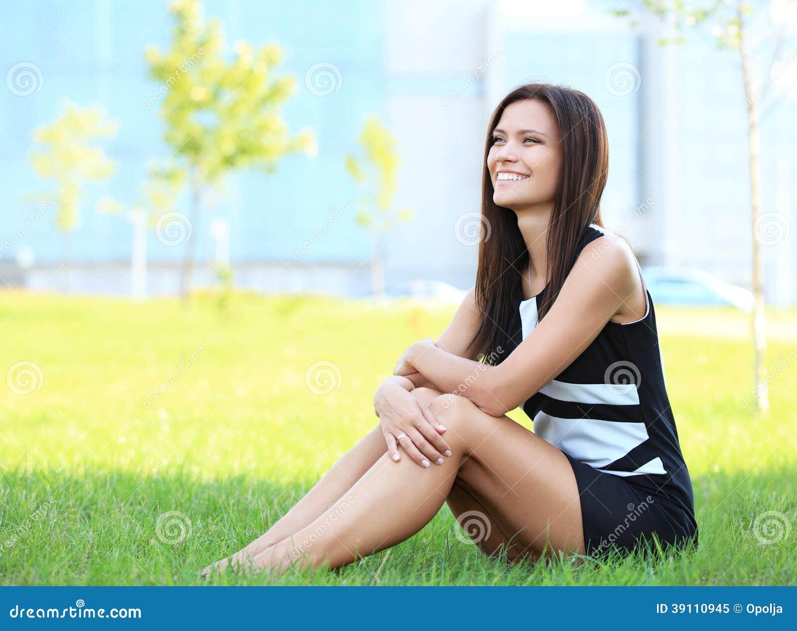 Bedrijfsvrouw die in openlucht op het gras zitten