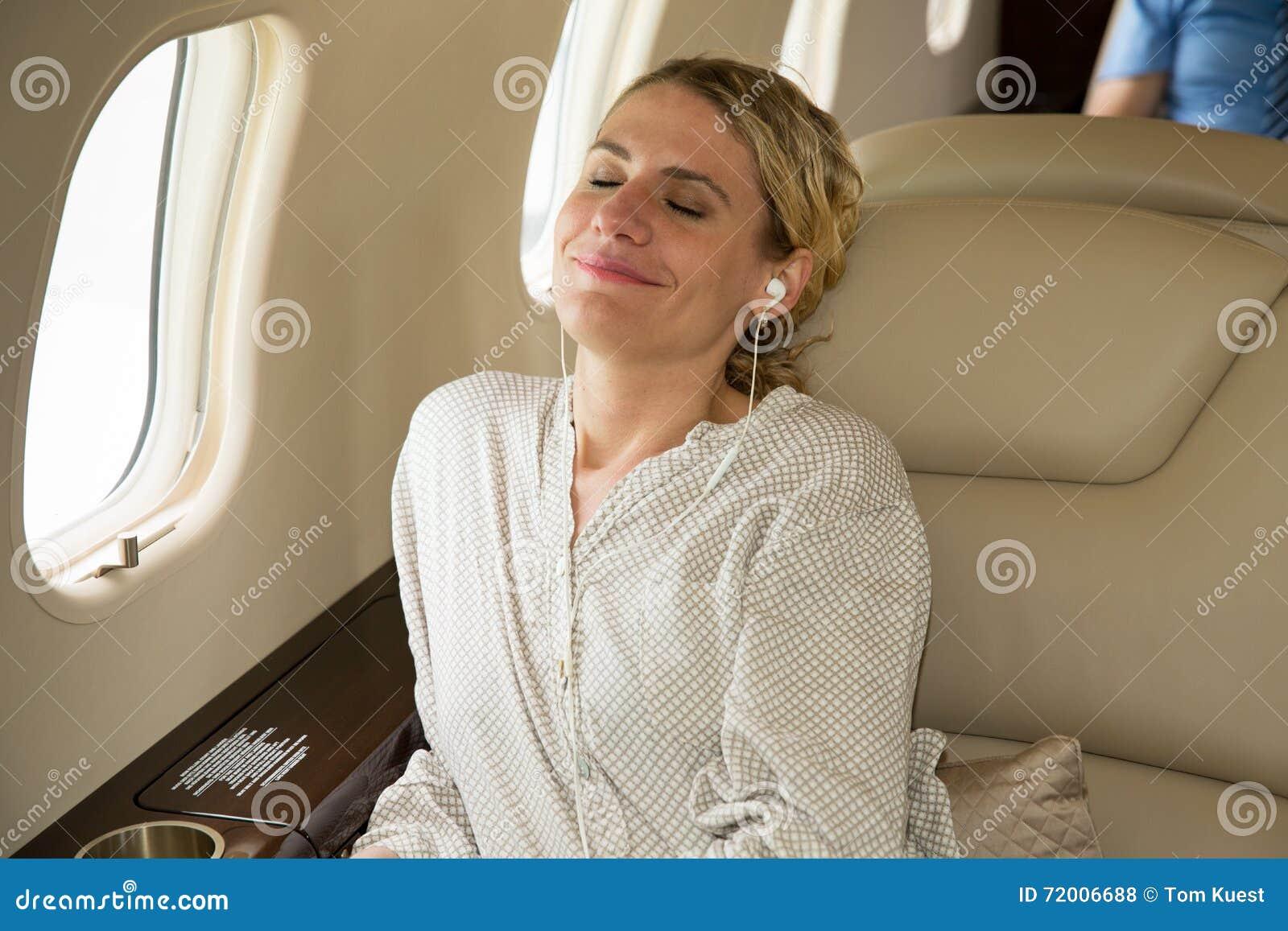 Bedrijfsvrouw in een collectieve straal die en aan musi ontspannen luisteren