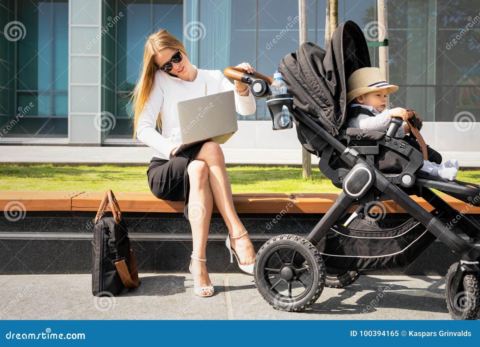Bedrijfsvrouw met kind in wandelwagen die op de telefoon spreken en aan laptop werken