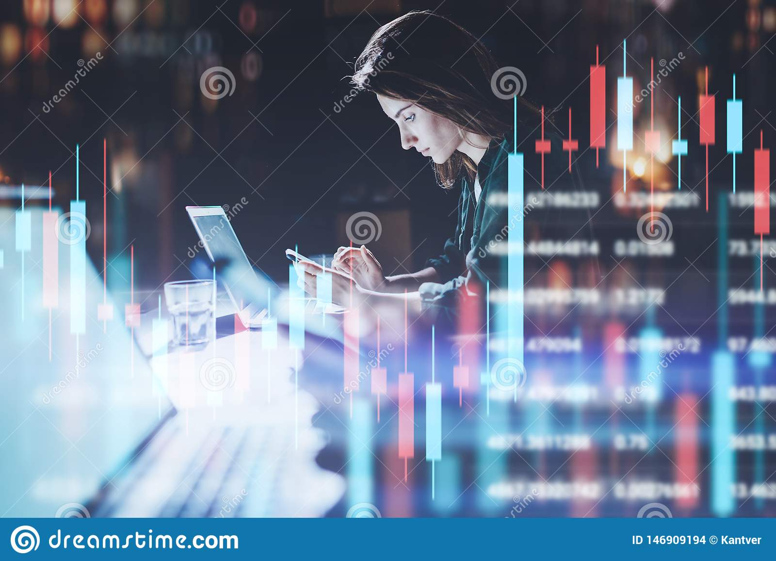 Bedrijfsvrouwenzitting op nachtkantoor vooraan laptop computer met financiële grafieken en het gebruiken van haar smartphone Rood