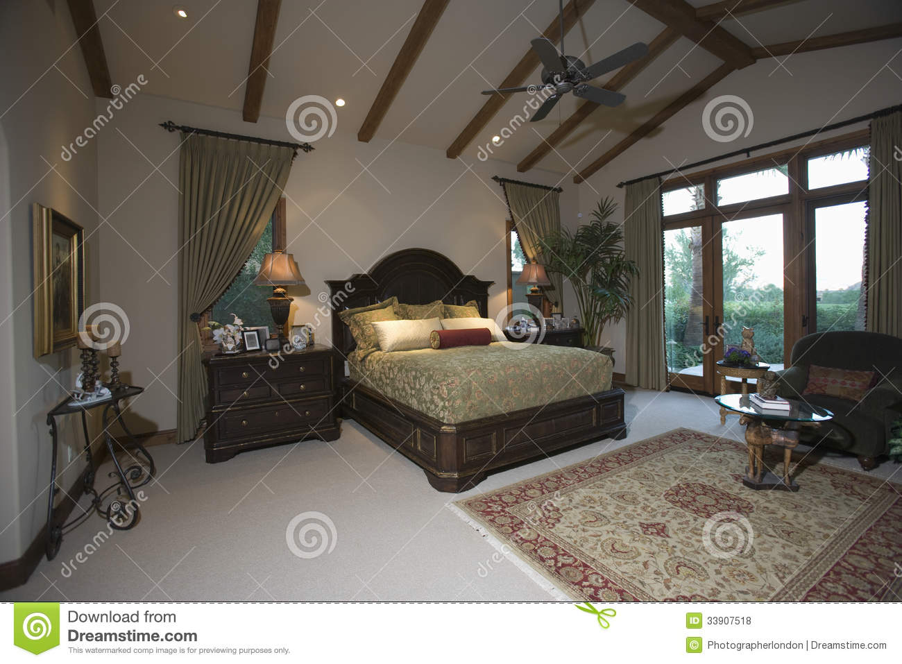 Bedroom With Beamed Ceiling And Patio Doors Stock Photo