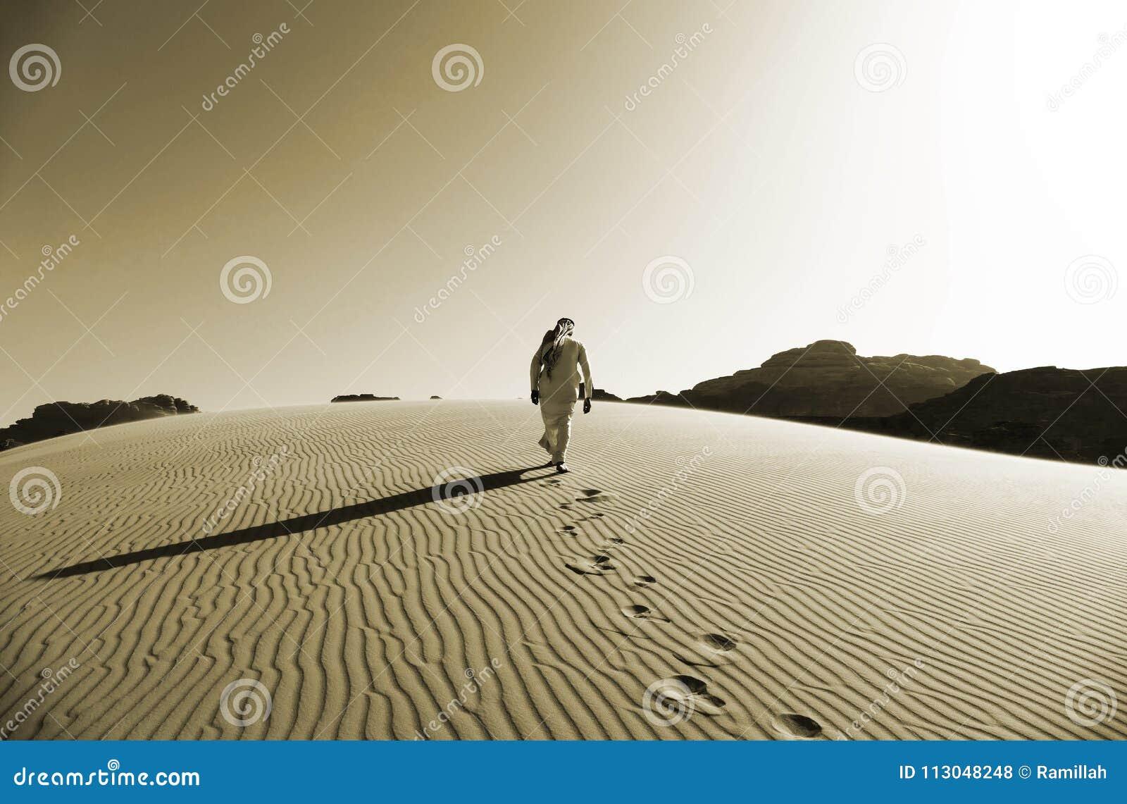 Beduíno que anda nas dunas de areia em Wadi Rum Desert, Jordânia na cor do Sepia