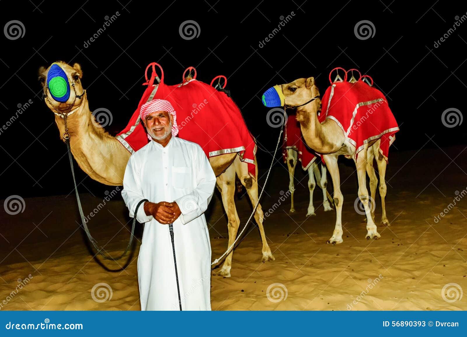 Beduino che sta davanti al suo cammello nel deserto arabo