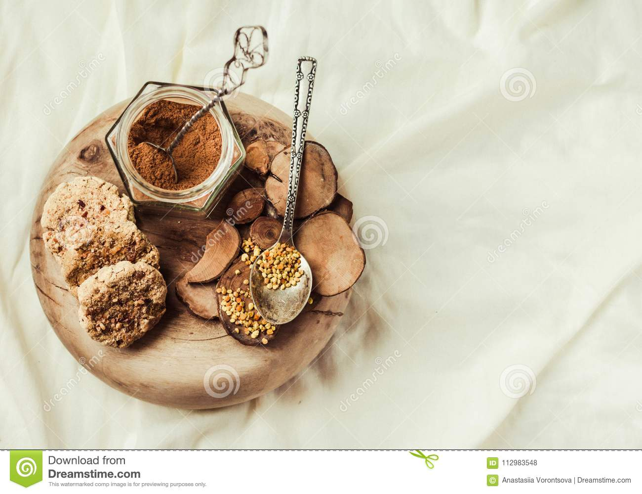 bee pollen in a jar on a wooden stand, Ceylon cinnamon and biscuits, white linen tablecloth background.Copy space.Top view.