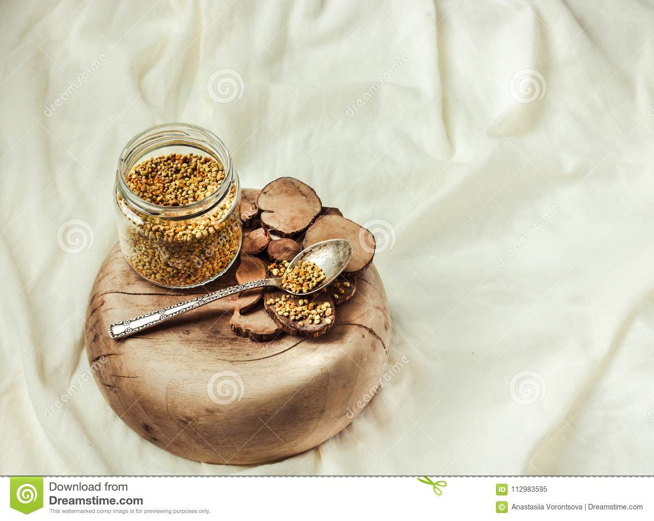 bee pollen in a jar on a wooden stand, white linen tablecloth.Place for text.Selective focus.
