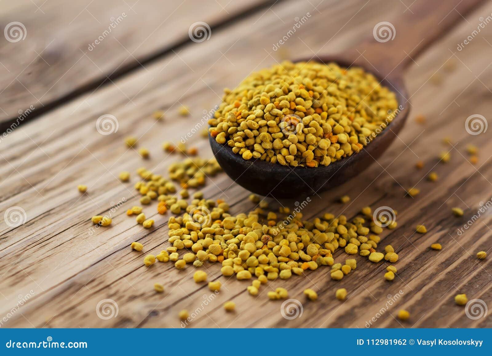 Bee pollen in spoon over wooden background. Healthy organic raw diet vegetarian food ingredient - bee pollen. Beekeeping products.