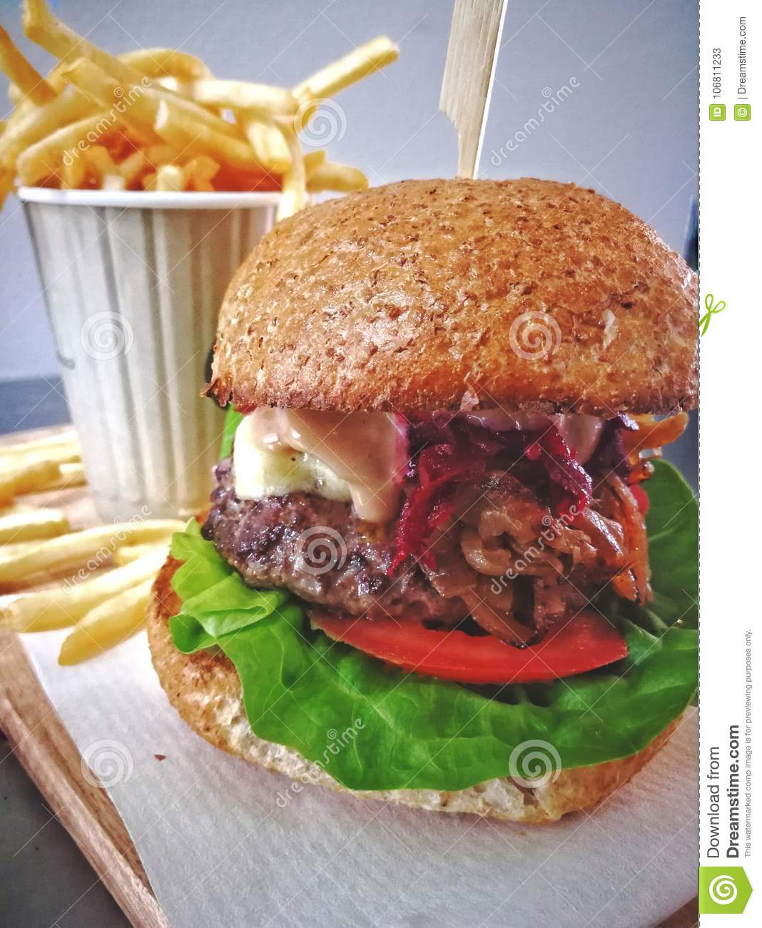 Beef burger with chips in background on wood tray