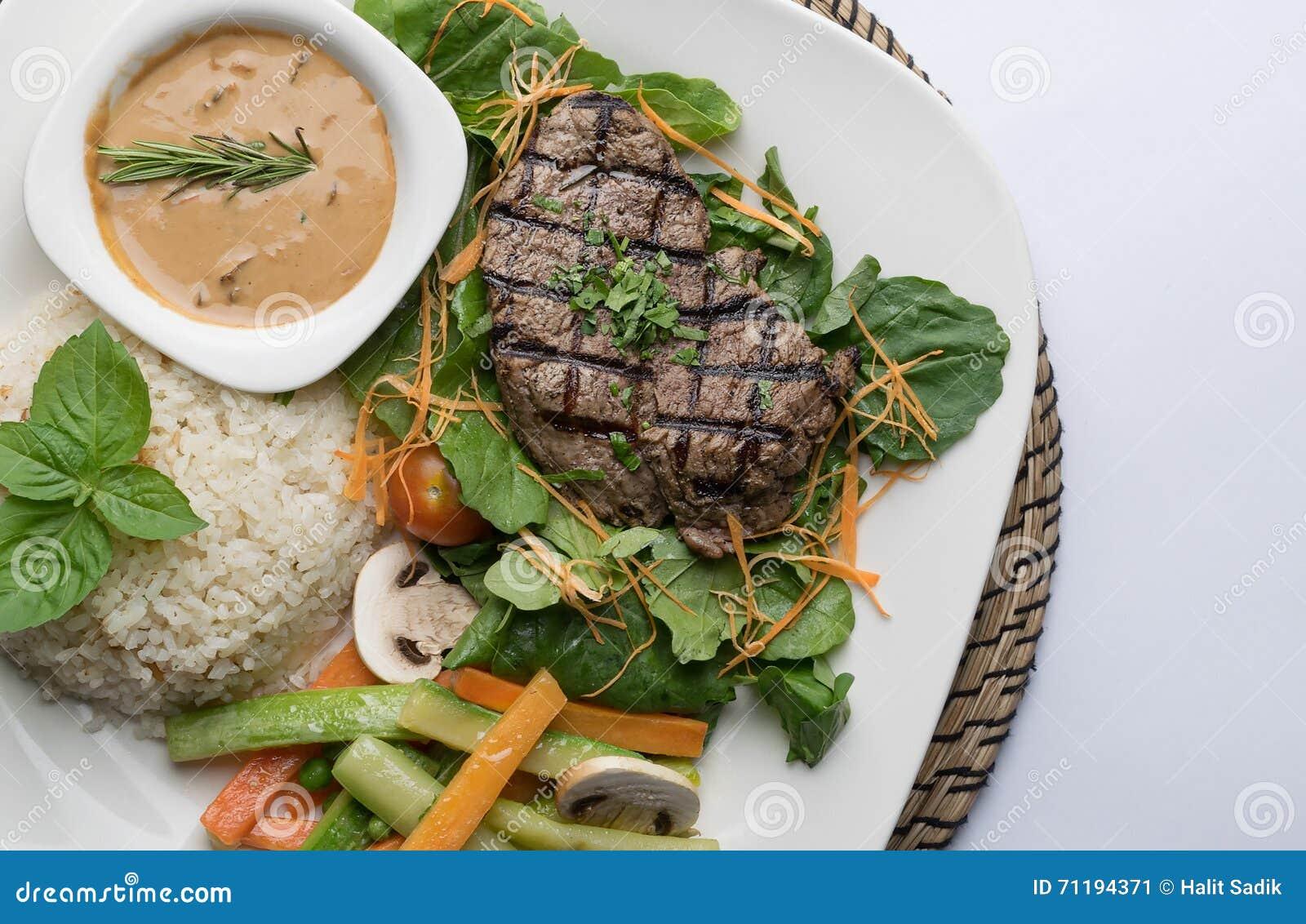 Beef filet steak served with rice, vegetables, and mushroom