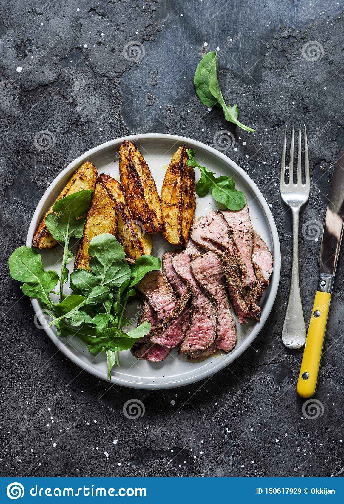 Beef steak and baked young potatoes - delicious lunch on a dark background, top view