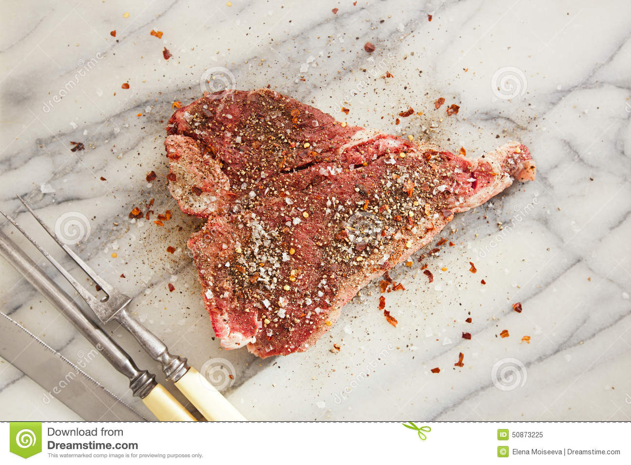 Beef steak t-bone with vintage meat fork on marble backdro