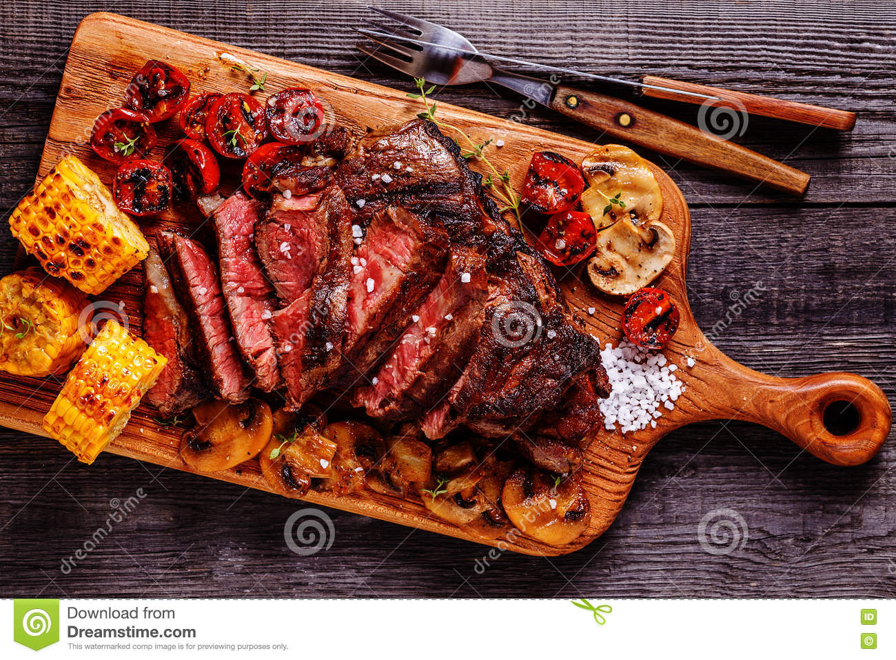 Beef steaks with grilled tomatoes, mushrooms and corn.
