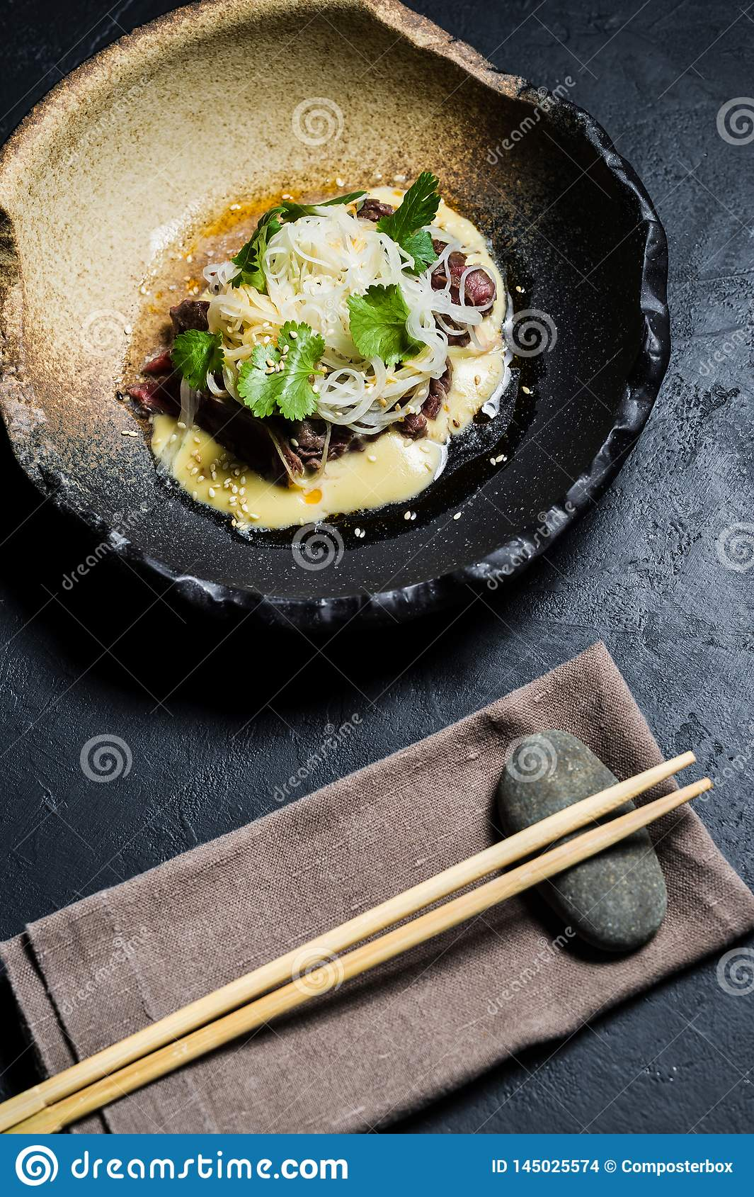 Beef tenderloin with sauce and glass noodles, dark background.
