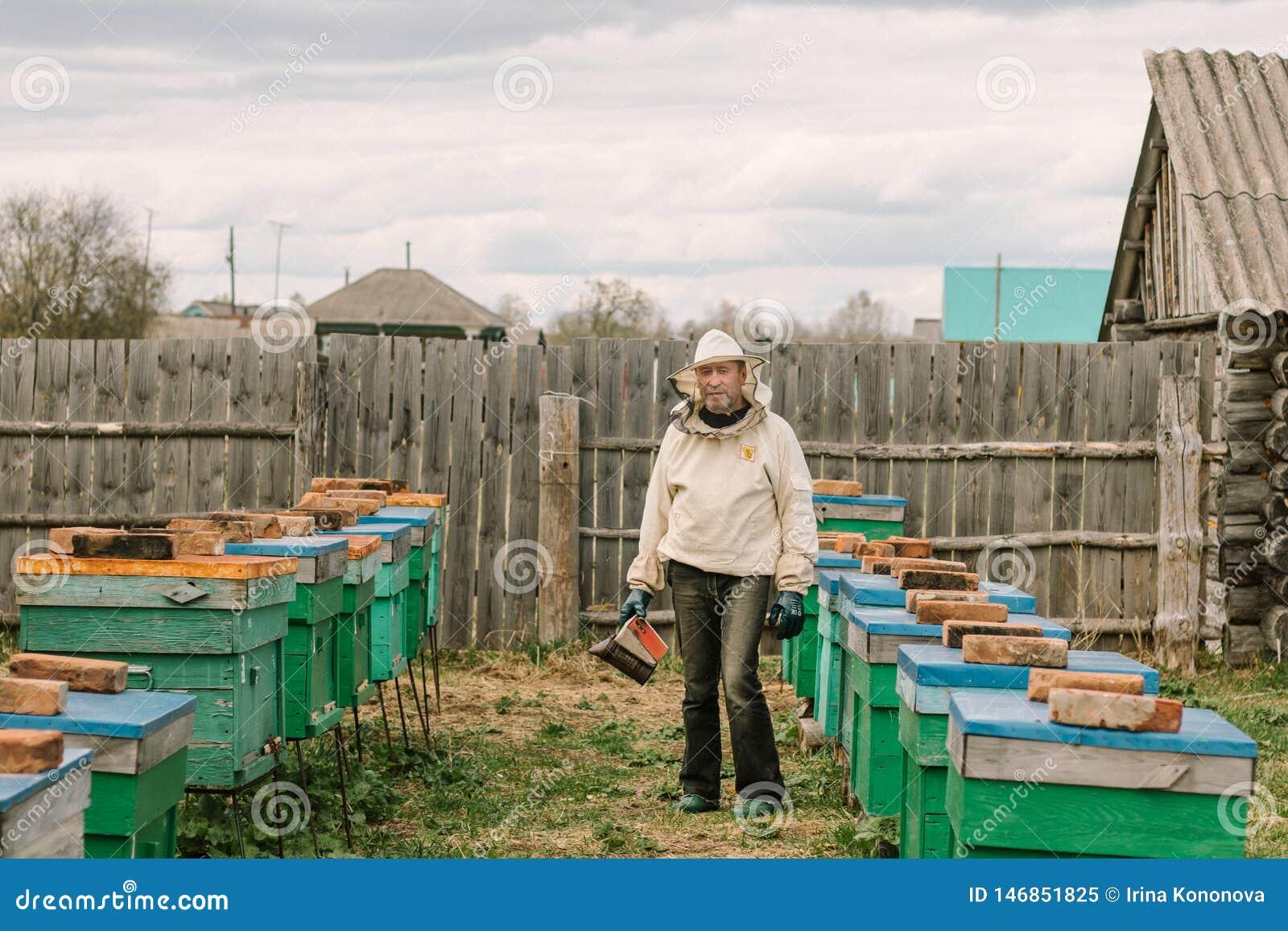 Beekeeper в защитном костюме среди крапивниц